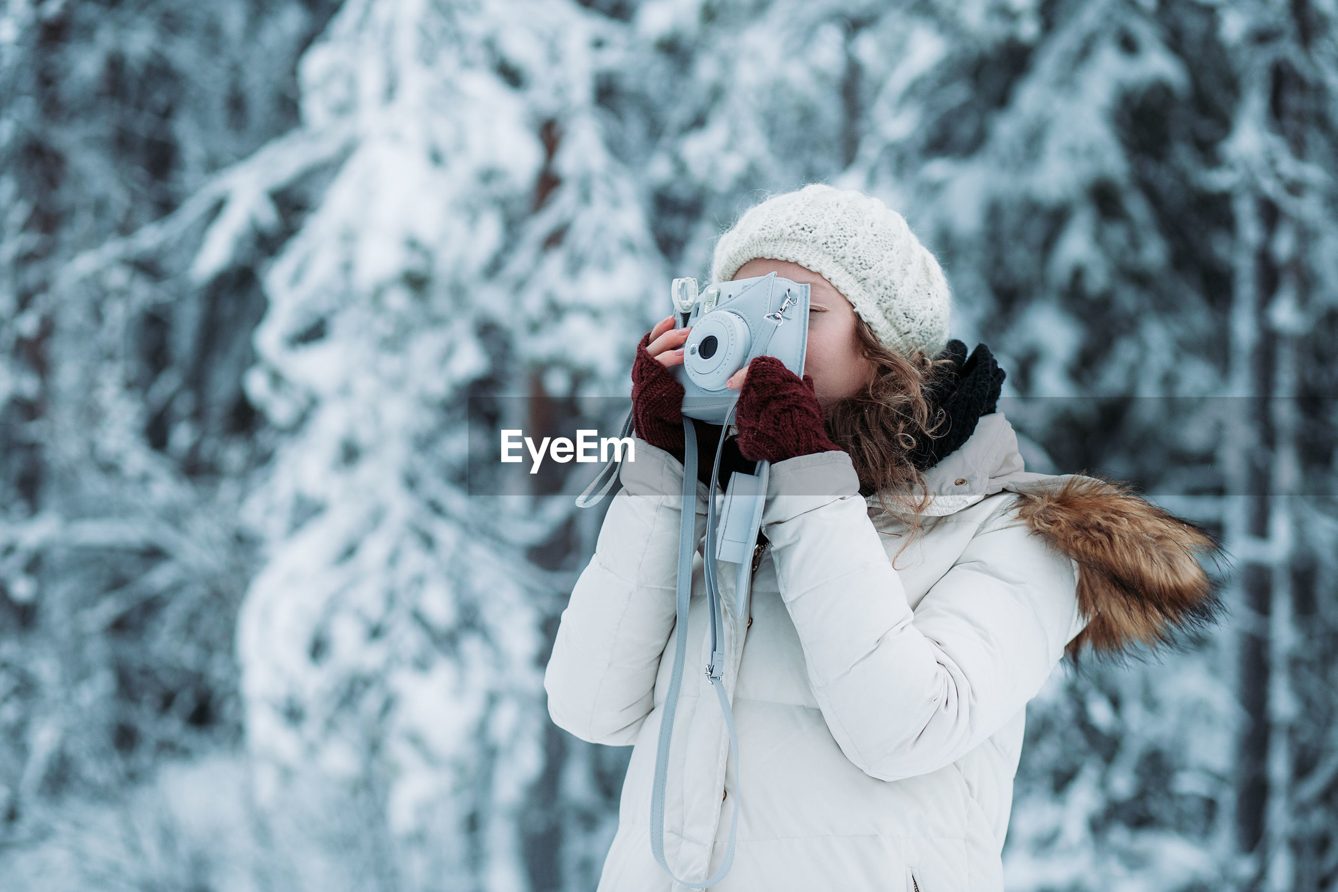 Young woman photographing from camera during winter