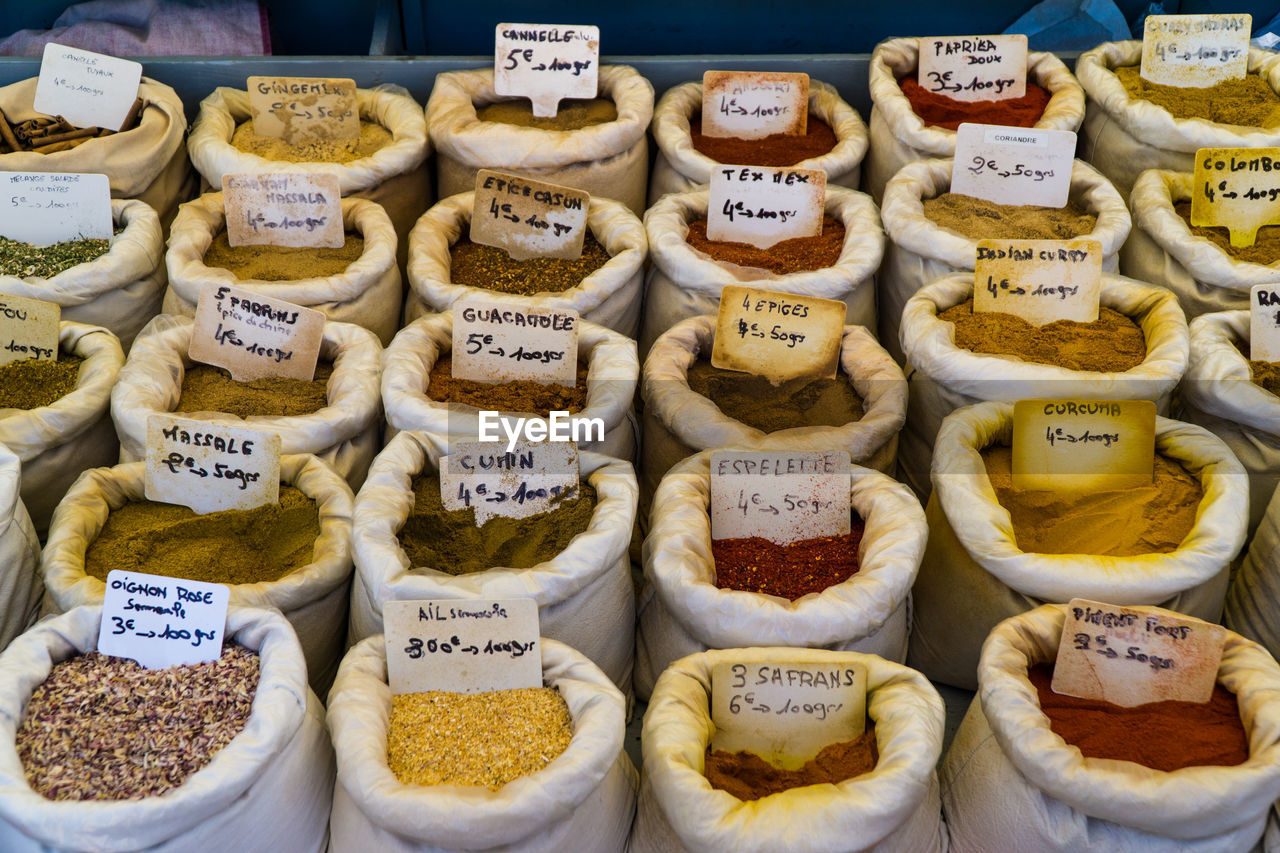 High Angle View Of Spices With Labels In Sacks At Market Stall