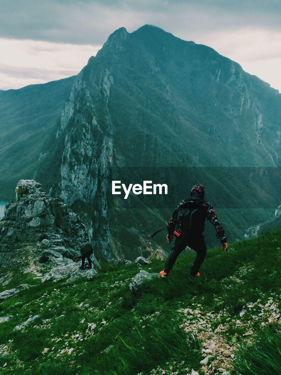 People Hiking On Grass Mountain