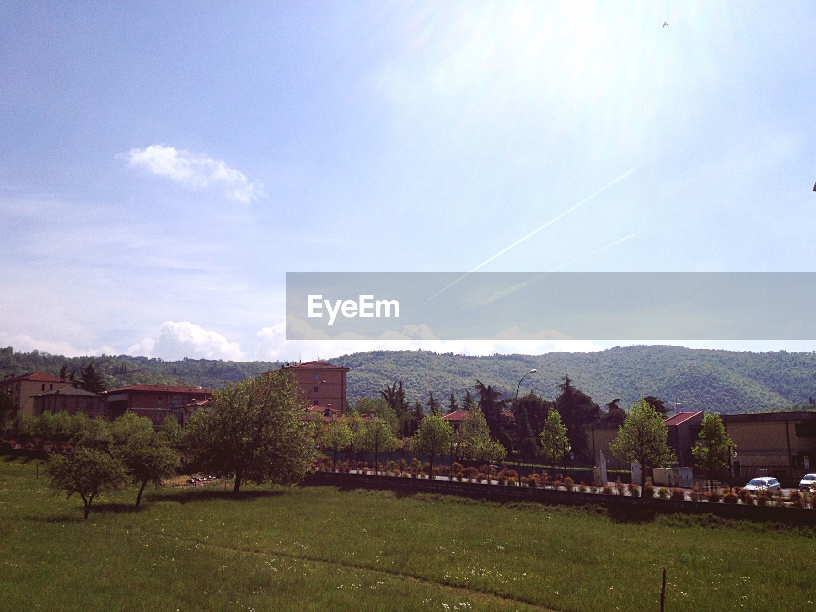 mountain, tree, landscape, sky, grass, tranquil scene, mountain range, tranquility, scenics, built structure, building exterior, beauty in nature, nature, architecture, green color, field, house, sunlight, day, blue