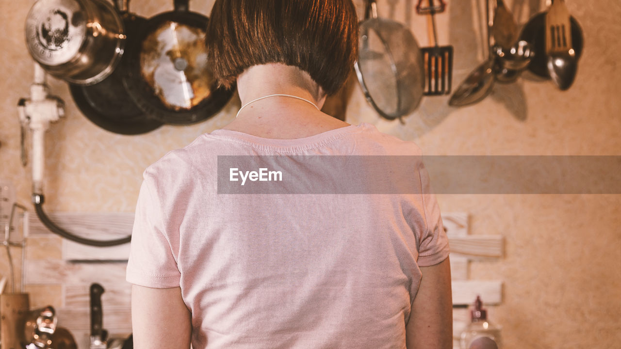 Rear View Of Woman Working In Kitchen At Home