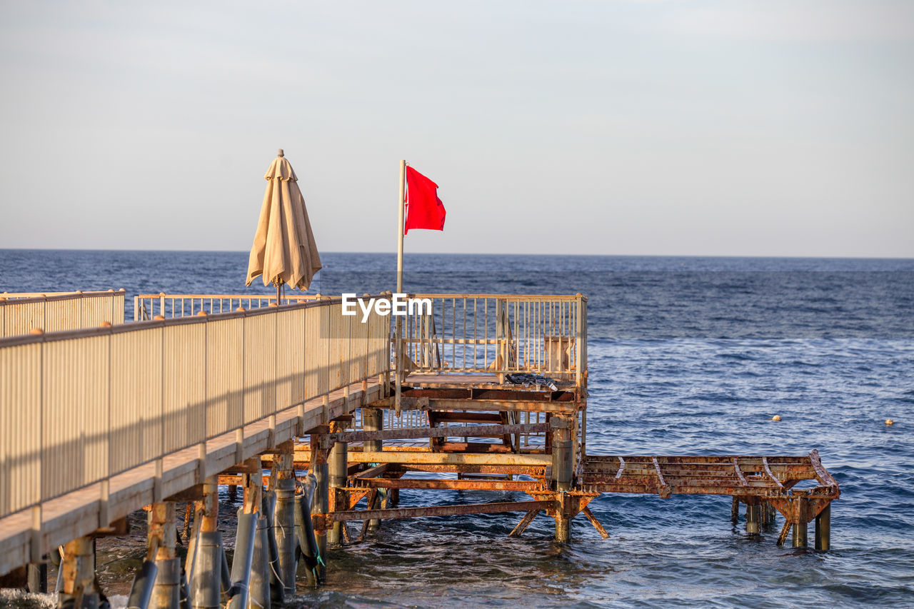 water, sea, horizon over water, horizon, sky, beauty in nature, scenics - nature, nature, no people, flag, day, wood - material, tranquil scene, tranquility, beach, transportation, land, outdoors, architecture