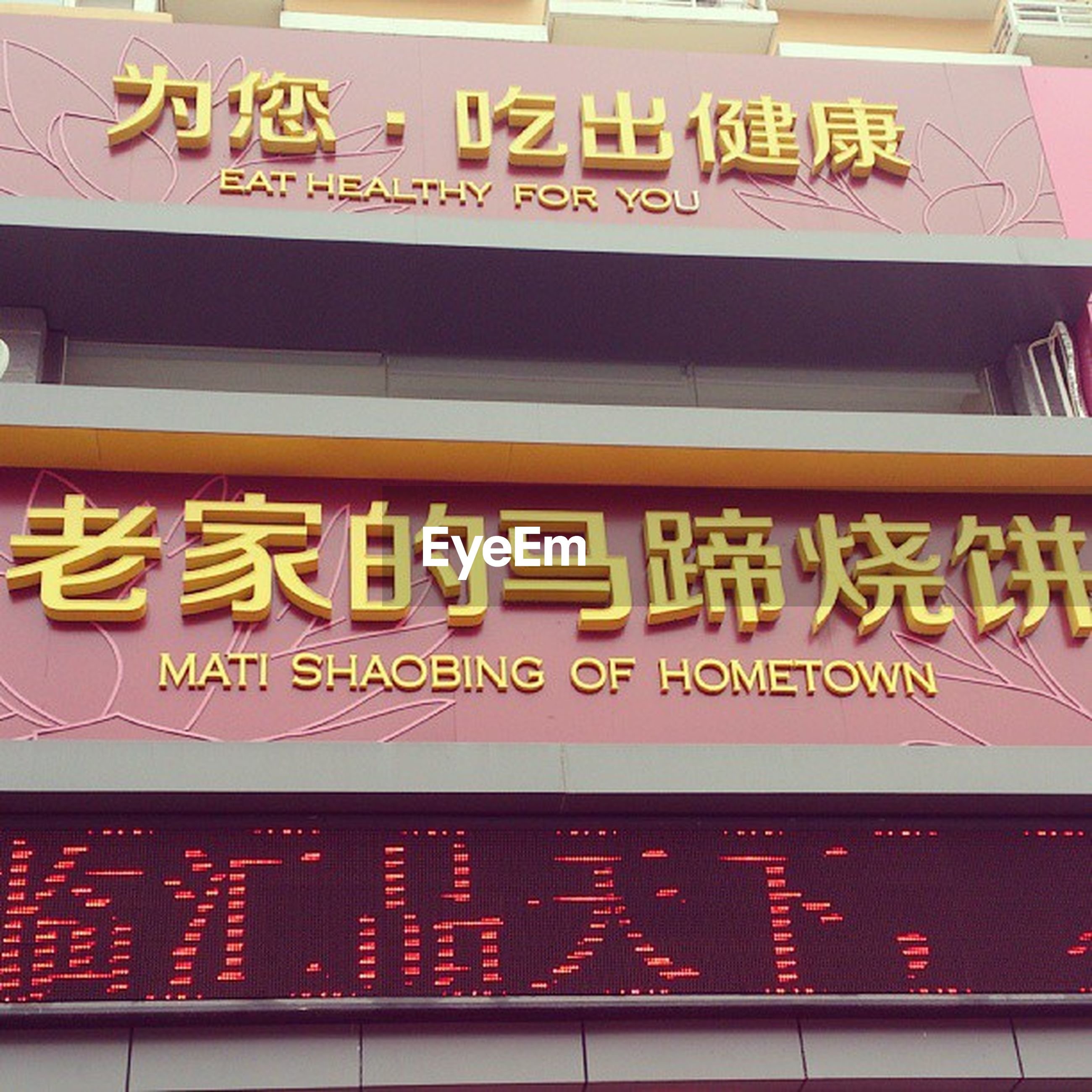 text, western script, communication, information sign, capital letter, non-western script, information, sign, yellow, architecture, commercial sign, guidance, built structure, low angle view, building exterior, advertisement, arrow symbol, illuminated, directional sign, no people