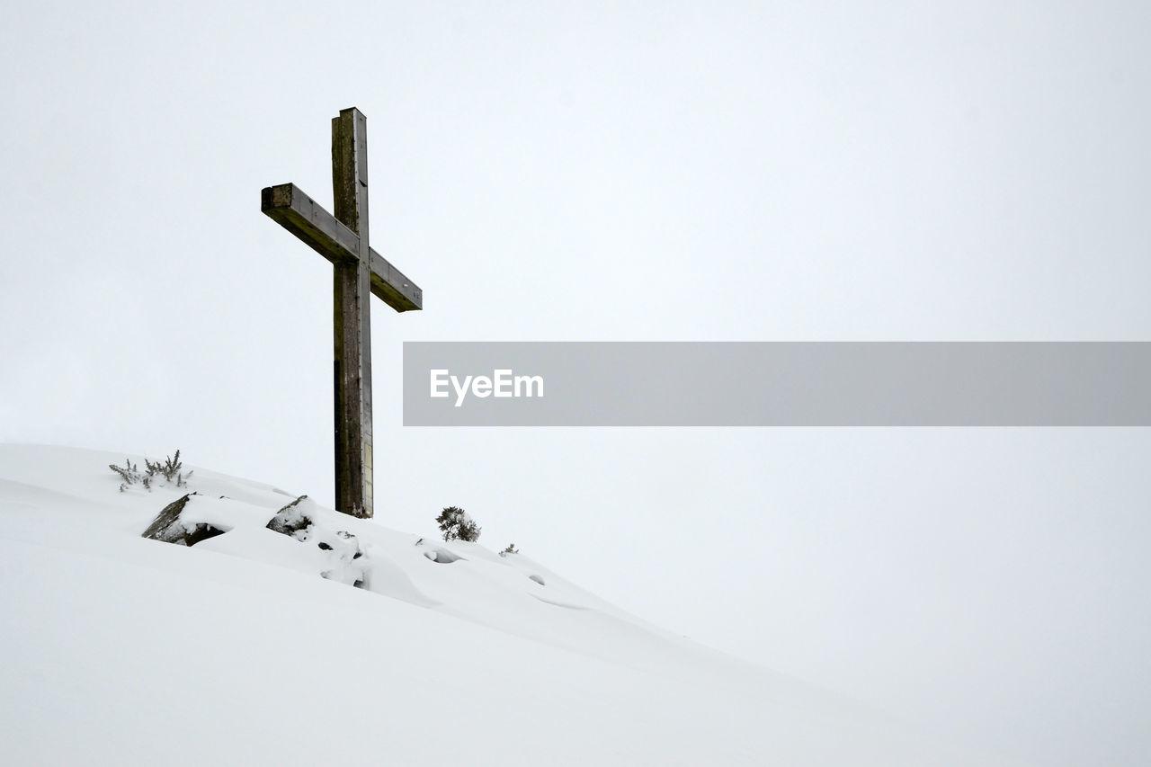 Cross on snow against clear sky