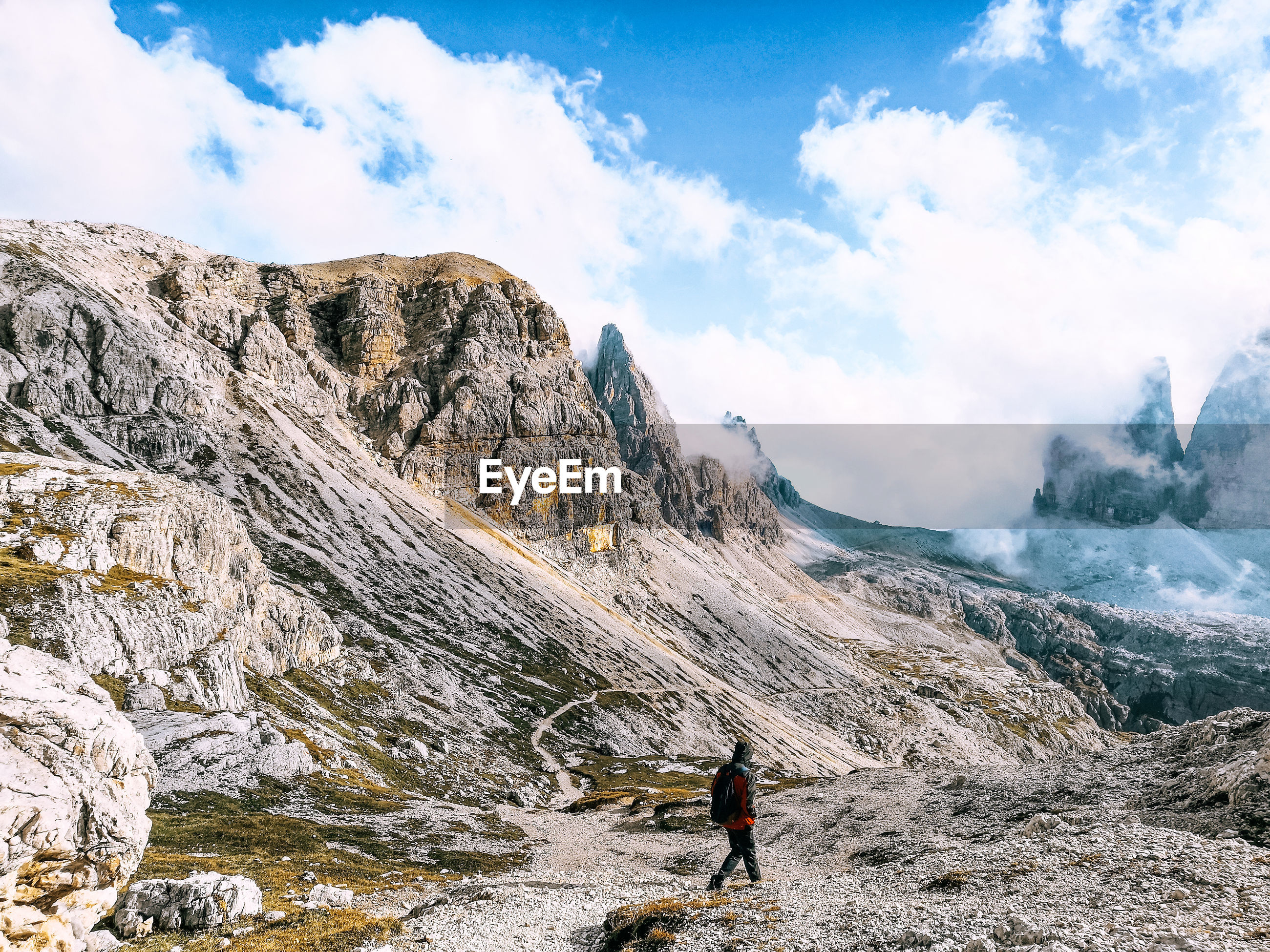Man walking on rocks by mountains against sky