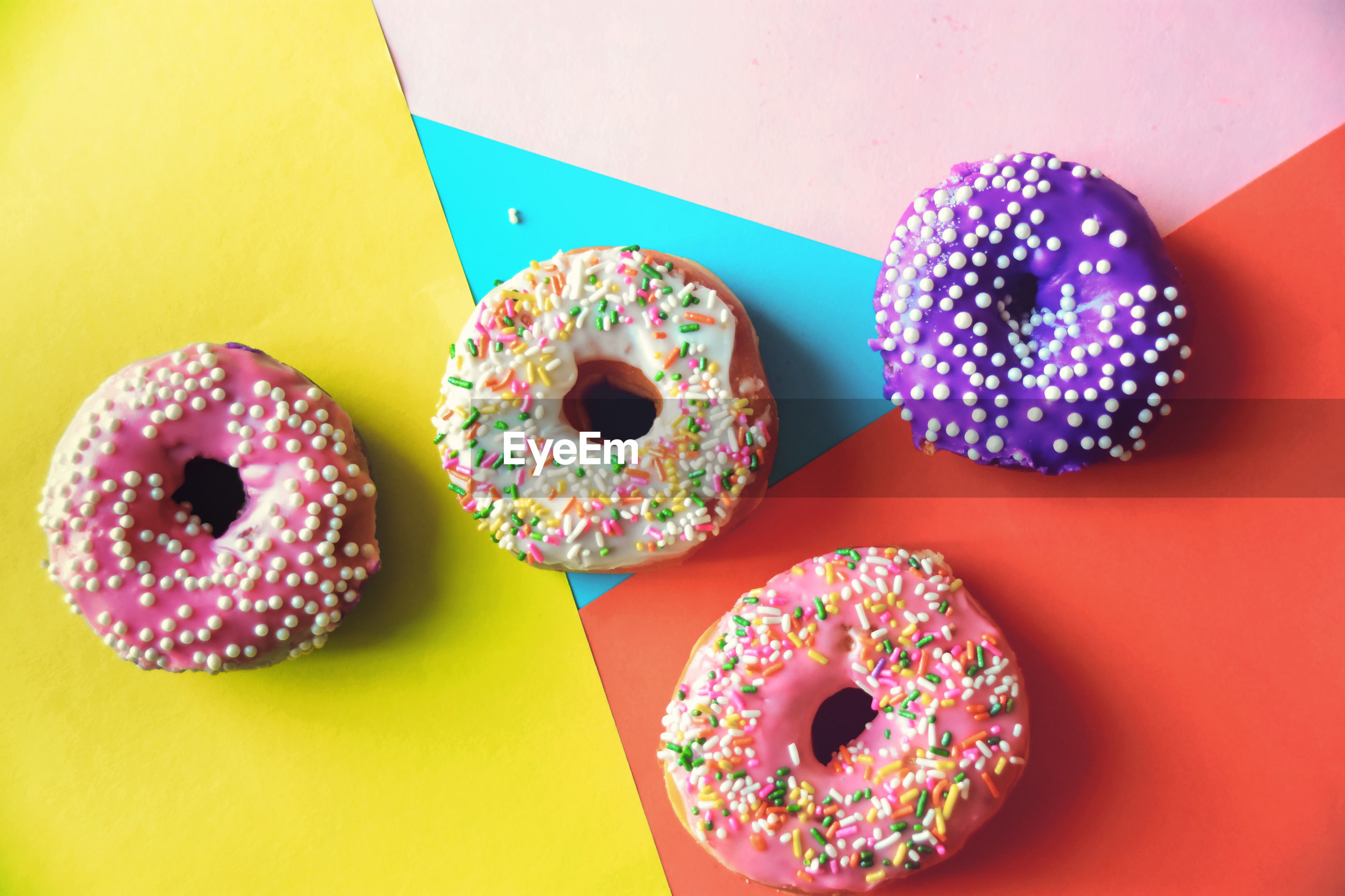 High angle view of multi colored donuts on table