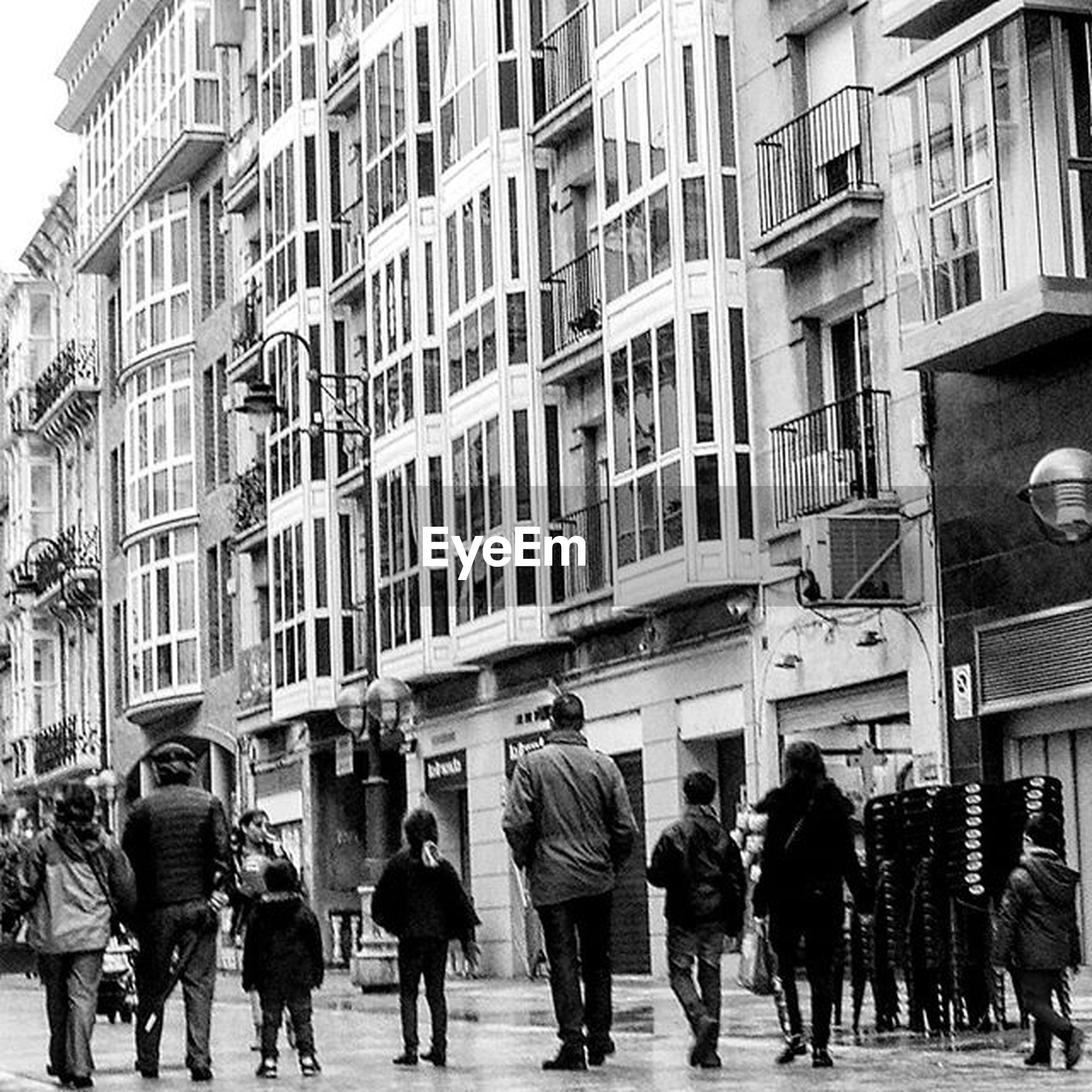 large group of people, architecture, building exterior, built structure, men, person, city, walking, city life, street, lifestyles, building, leisure activity, day, crowd, mixed age range, city street, outdoors, window