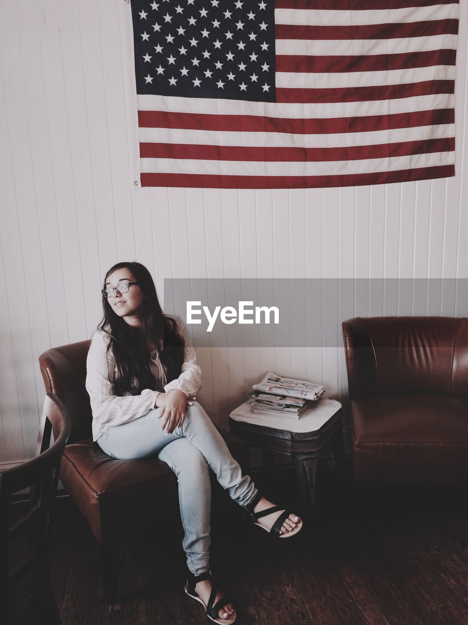Full Length Of Woman Sitting On Chair Against American Flag On Wall At Home