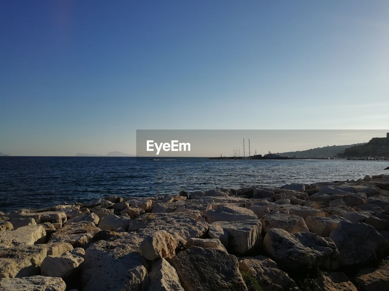 sea, sky, rock, water, rock - object, solid, copy space, scenics - nature, beauty in nature, nature, tranquil scene, no people, tranquility, clear sky, land, horizon, beach, day, outdoors, horizon over water, groyne, rocky coastline