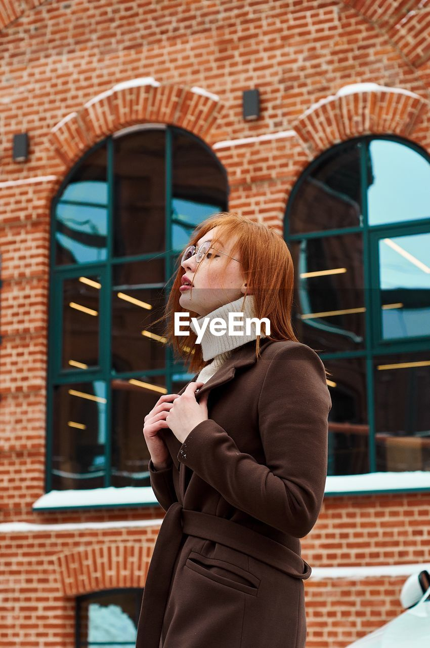 Woman looking away while standing against building