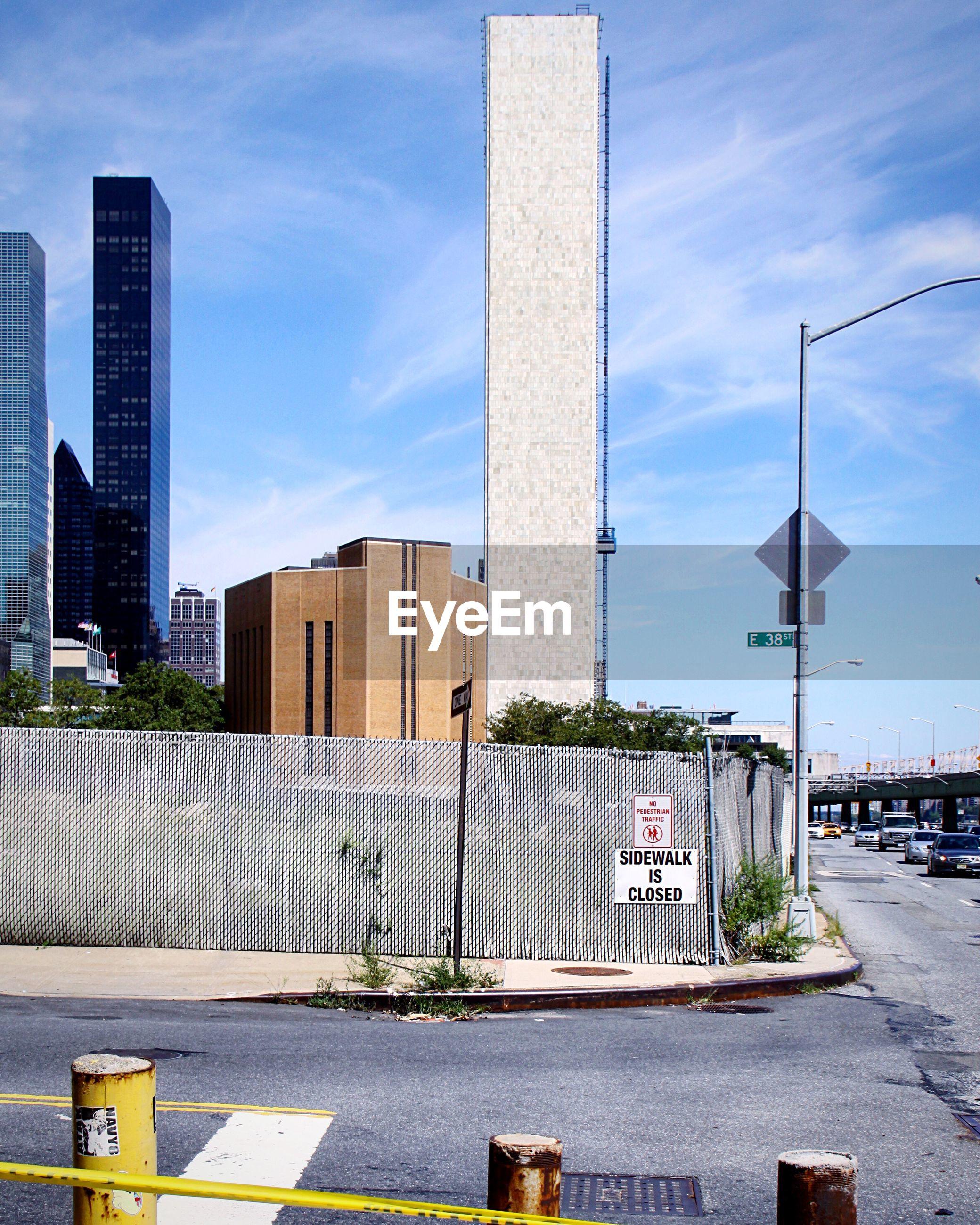ROAD BY MODERN BUILDINGS AGAINST SKY