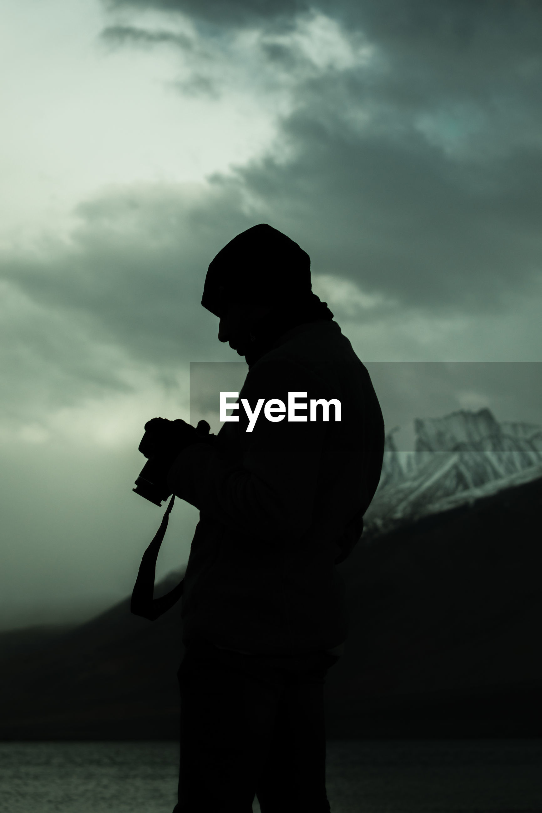 Silhouette of a photographer looking at a camera.