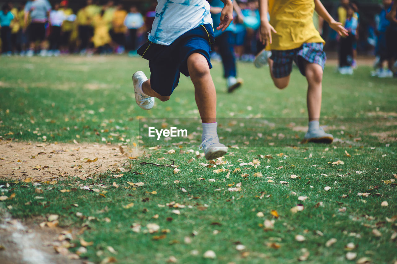 Low Section Of Boys Running On Grassy Field