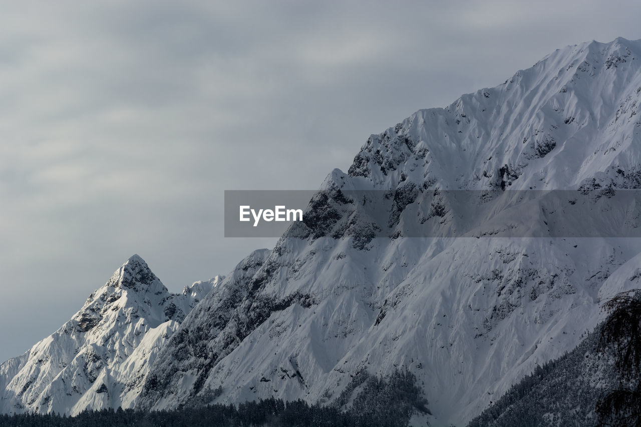 cold temperature, winter, mountain, snow, scenics - nature, beauty in nature, sky, cloud - sky, tranquil scene, snowcapped mountain, mountain range, tranquility, white color, non-urban scene, nature, environment, day, landscape, no people, mountain peak, outdoors, formation