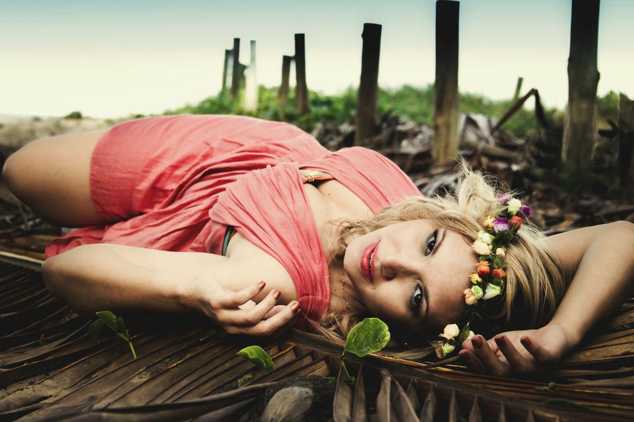 Beautiful Fashion Model Lying On Dry Palm Leaf