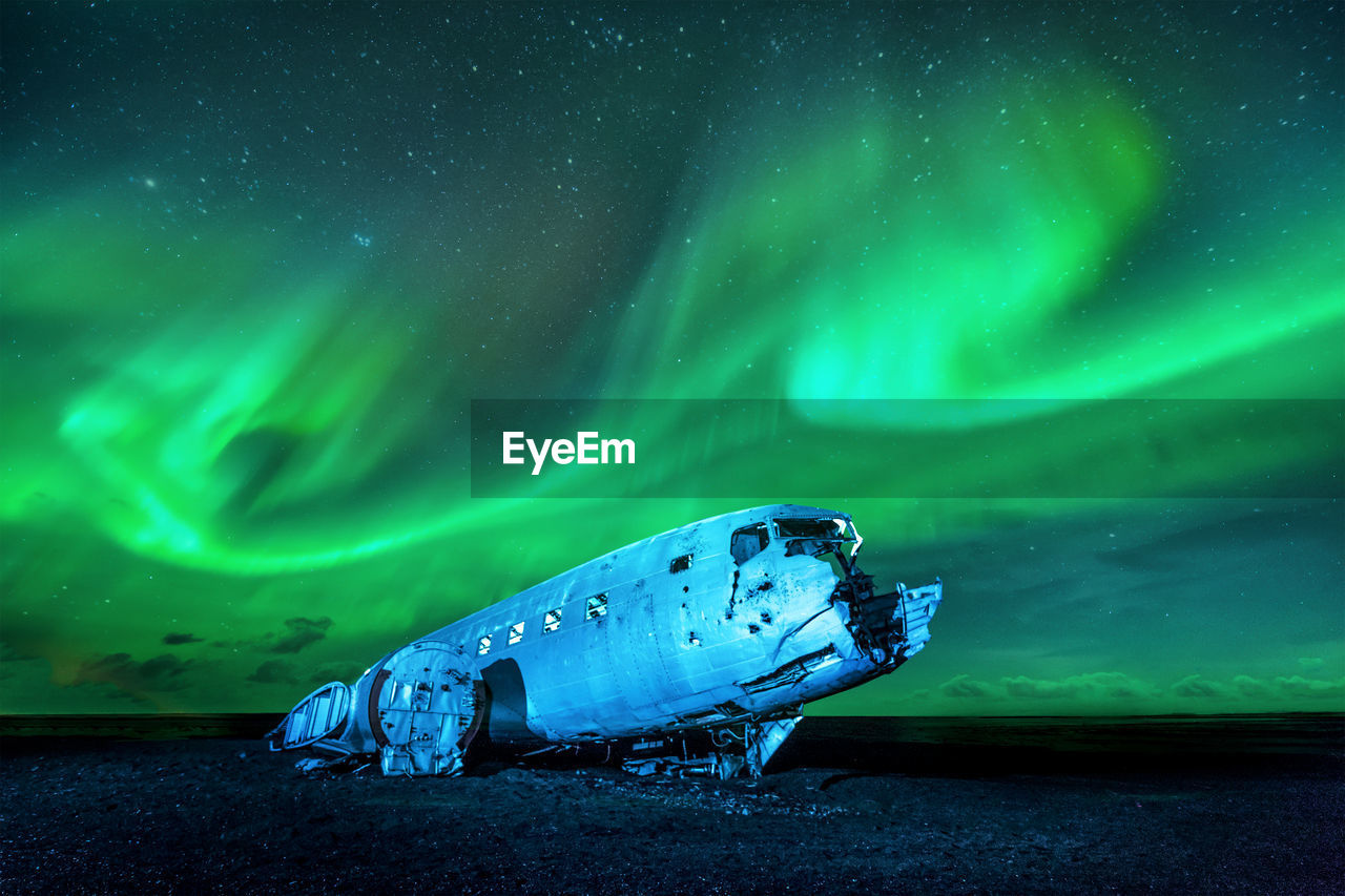 Wrecked military plane against northern lights