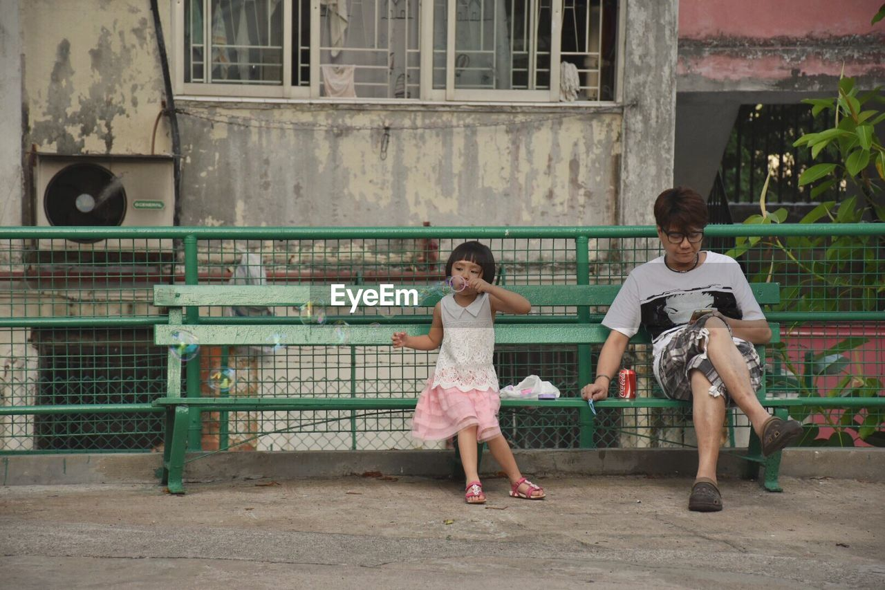 full length, childhood, building exterior, real people, built structure, day, architecture, elementary age, leisure activity, outdoors, casual clothing, two people, sitting, playing, lifestyles, togetherness, friendship, girls, boys, city, young adult, people