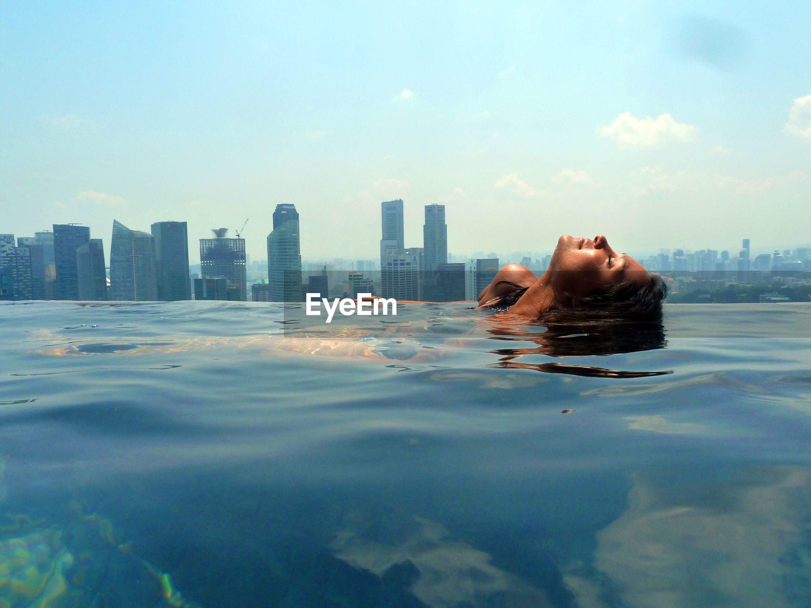 Woman relaxing in swimming pool with cityscape in background