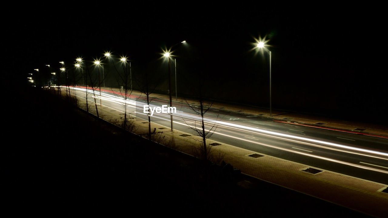Light Trails Over Illuminated Street At Night