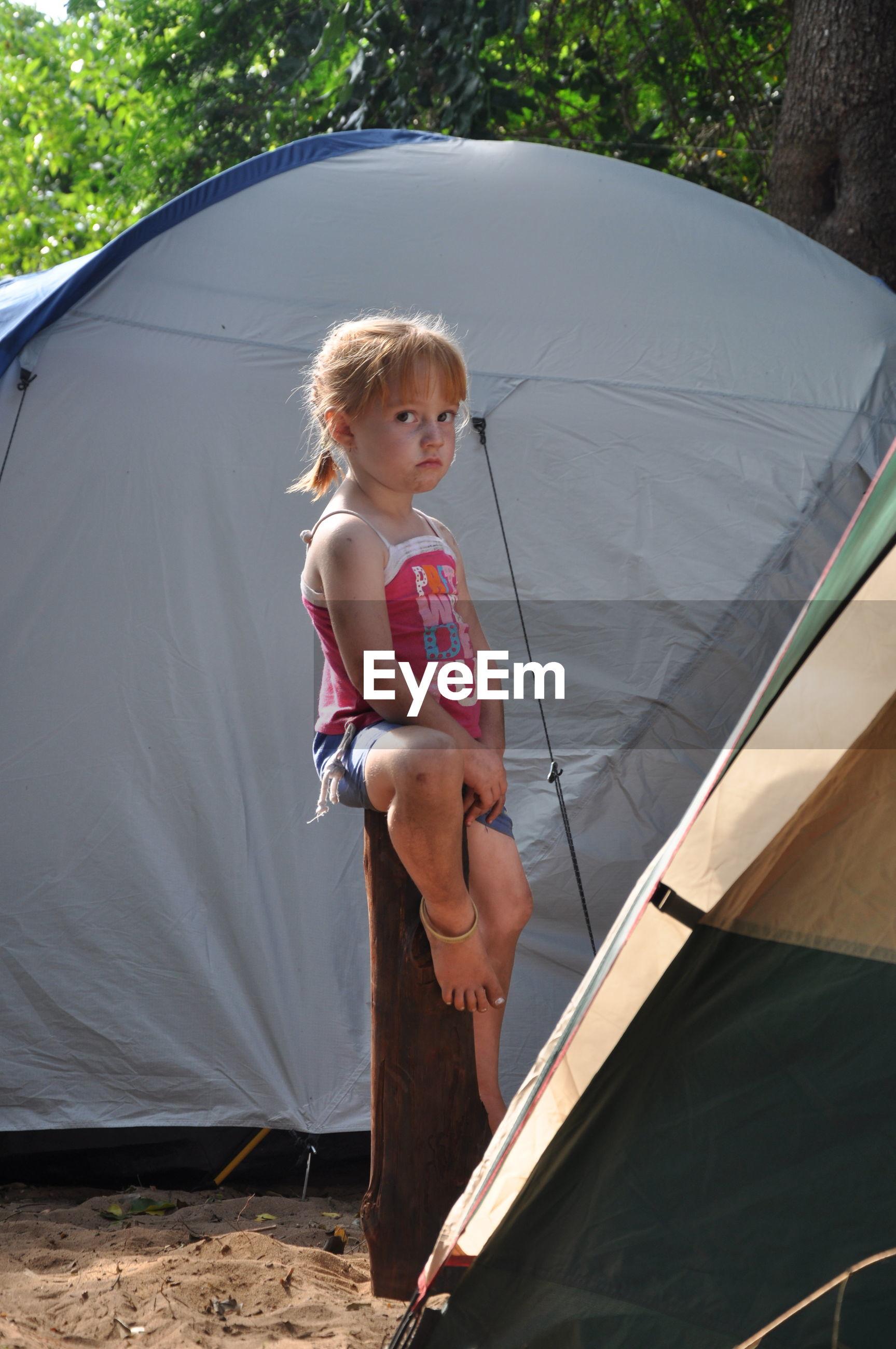Portrait of girl sitting on wooden stump against tent