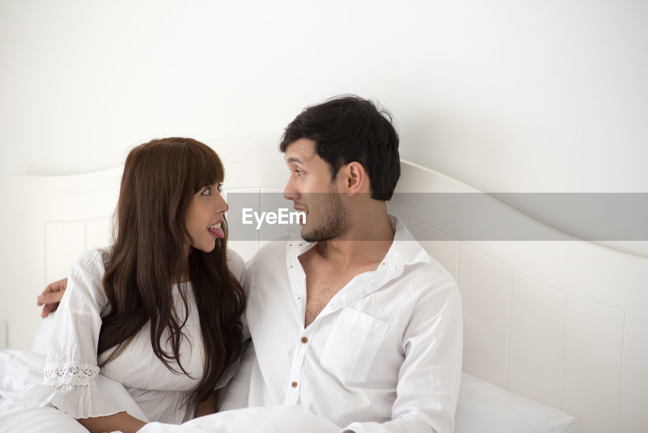 young women, young adult, two people, couple - relationship, togetherness, young men, love, women, indoors, adult, bonding, young couple, heterosexual couple, lifestyles, emotion, waist up, men, real people, positive emotion