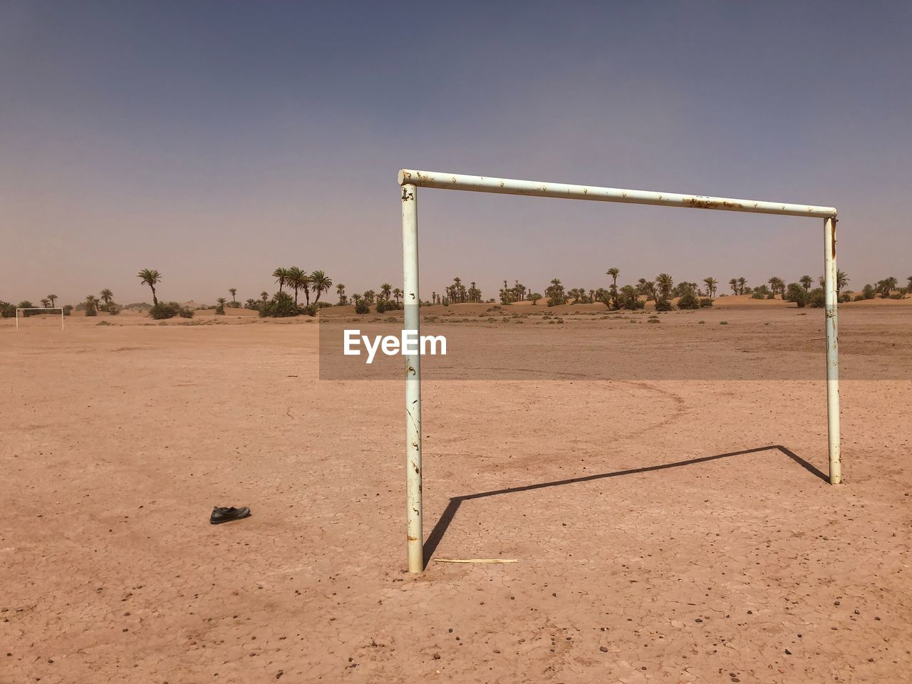 sport, sky, soccer, team sport, land, nature, goal post, day, playing field, soccer field, absence, no people, soccer goal, sports equipment, field, sunlight, clear sky, outdoors, plant, grass