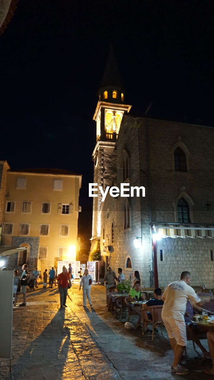 night, architecture, built structure, building exterior, illuminated, real people, large group of people, spirituality, religion, leisure activity, place of worship, lifestyles, men, outdoors, travel destinations, sky, women, bell tower, people