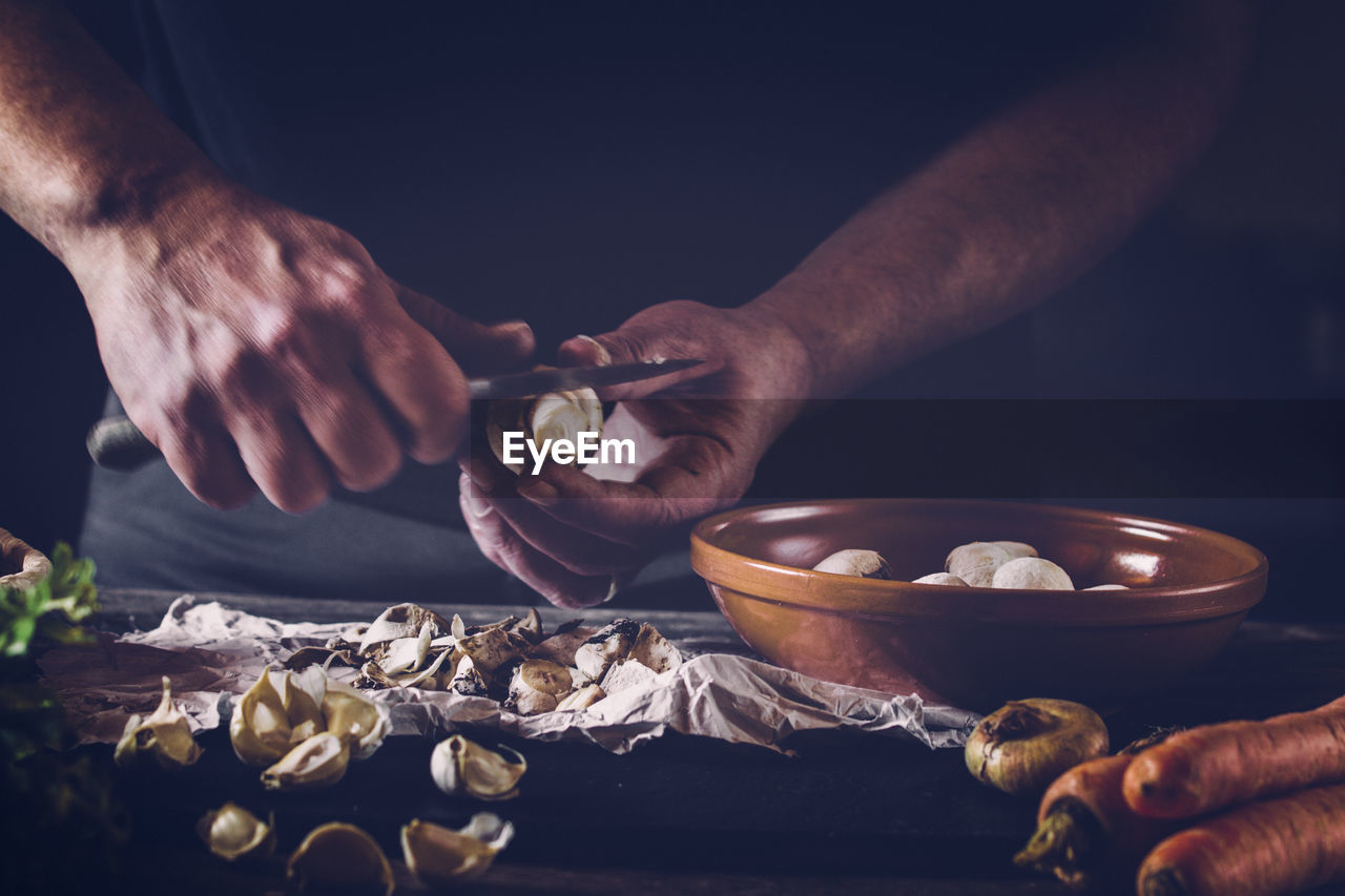 Cropped Image Of Chef Cutting Mushroom On Table