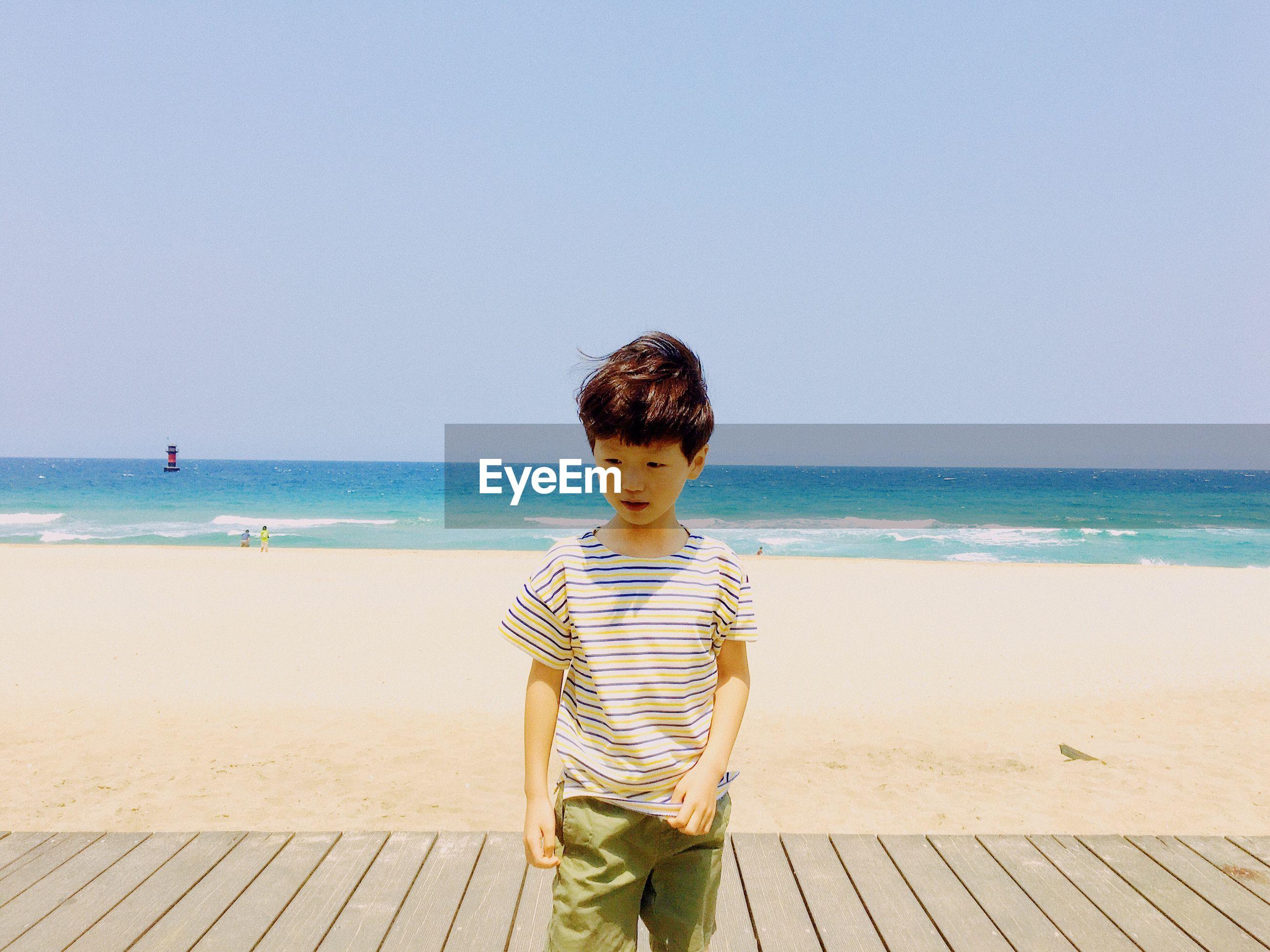 Boy On Boardwalk At Beach Against Clear Sky