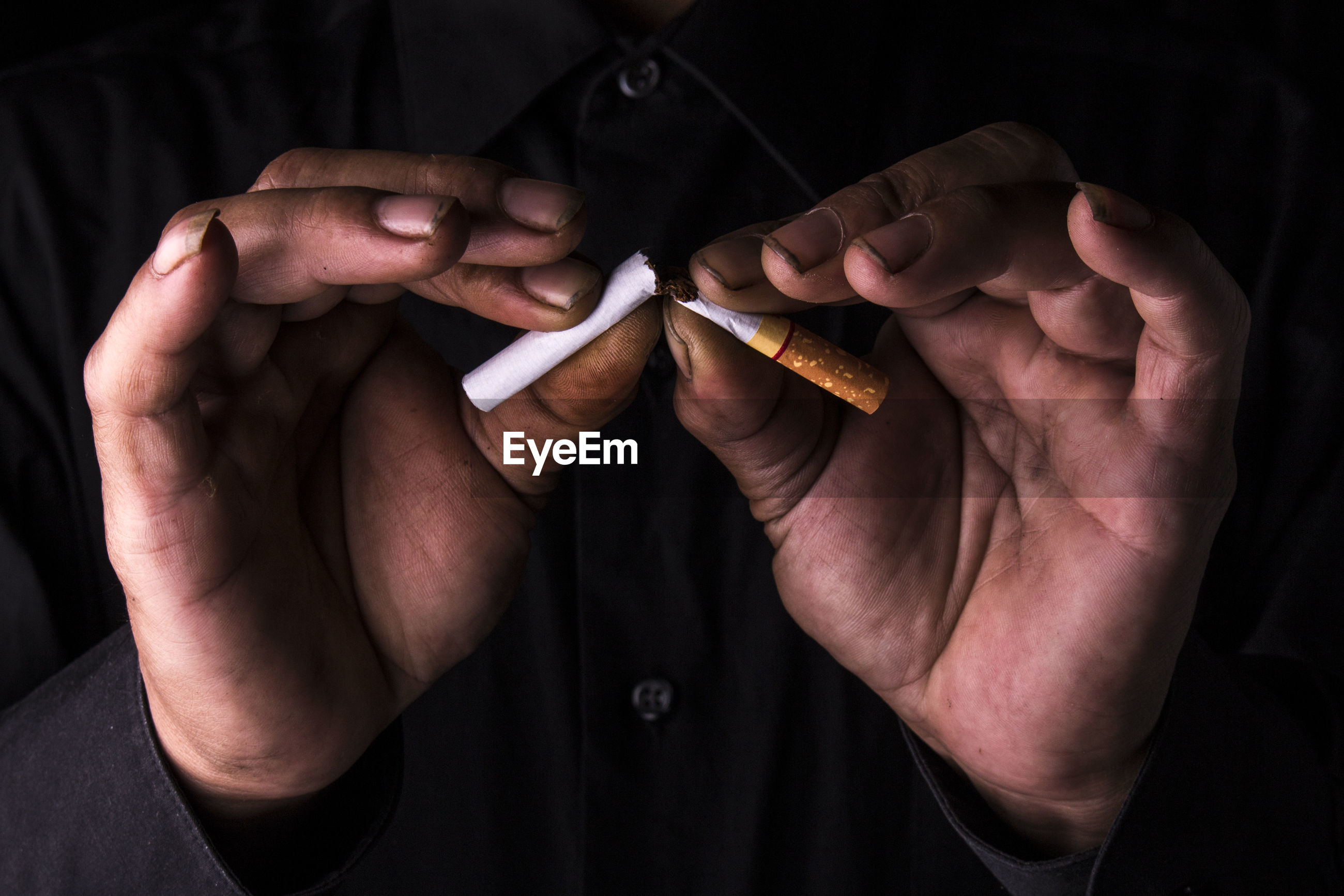 Midsection of man holding cigarette against black background