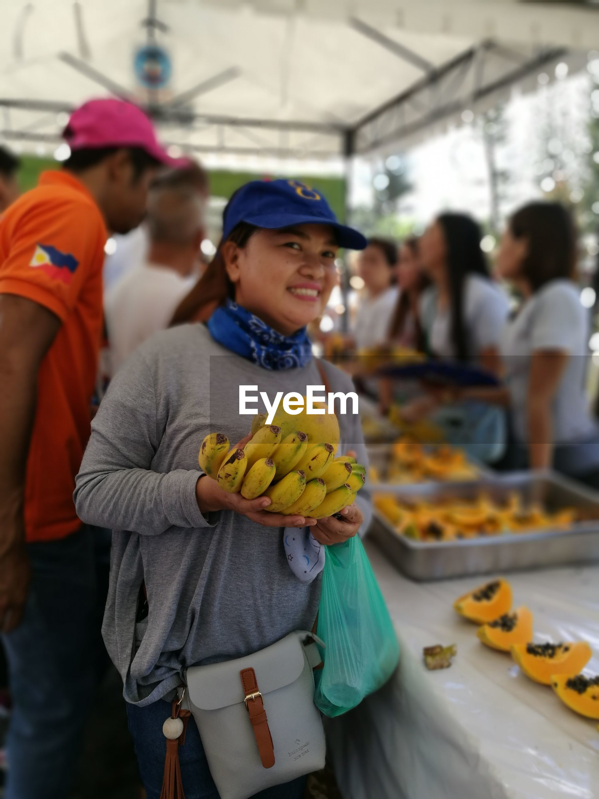 Happy mid adult woman with fruits standing at market