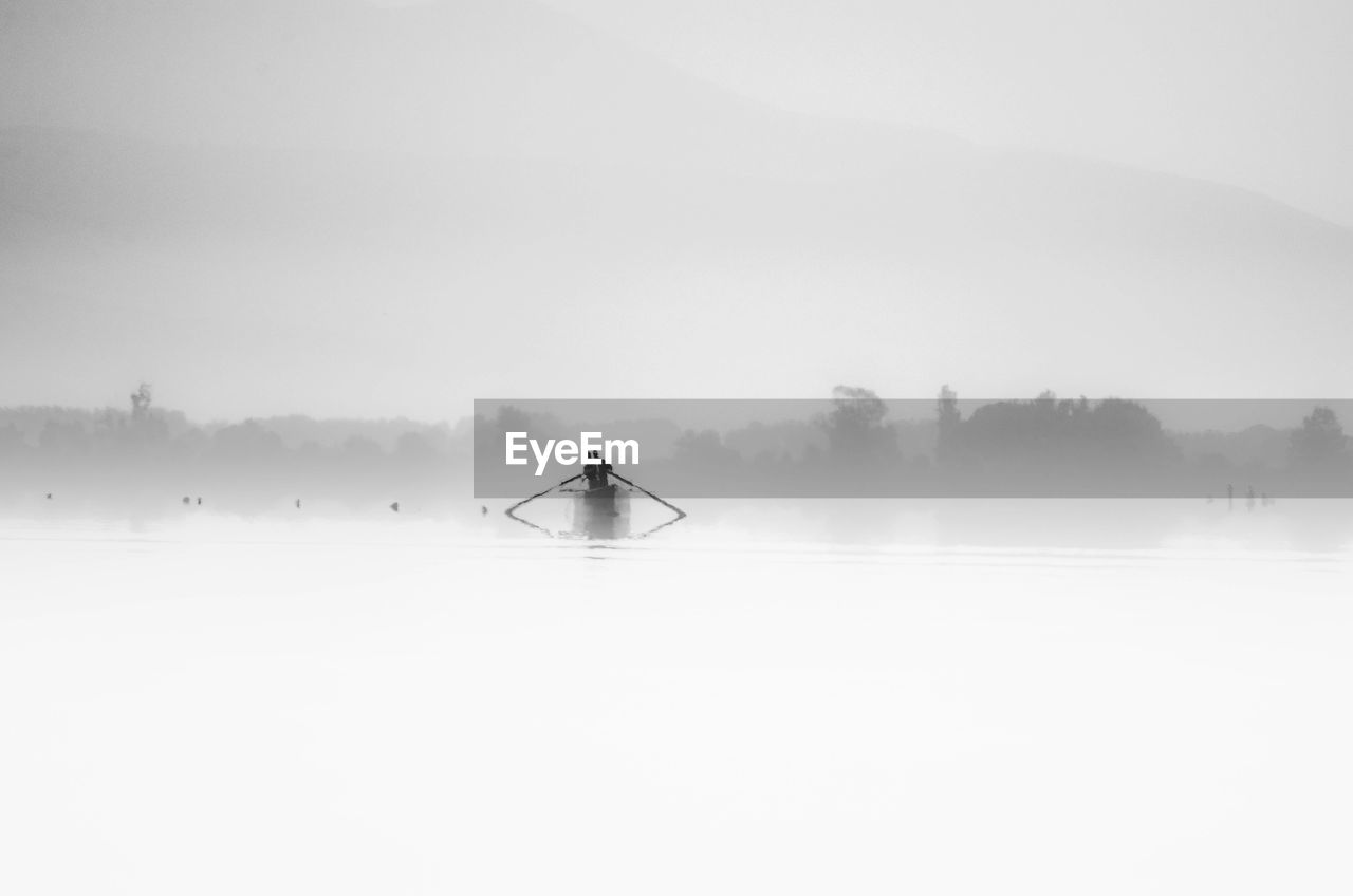 fog, water, beauty in nature, cold temperature, scenics - nature, tranquility, nature, real people, winter, one person, tranquil scene, non-urban scene, lake, sky, waterfront, day, lifestyles, nautical vessel, outdoors