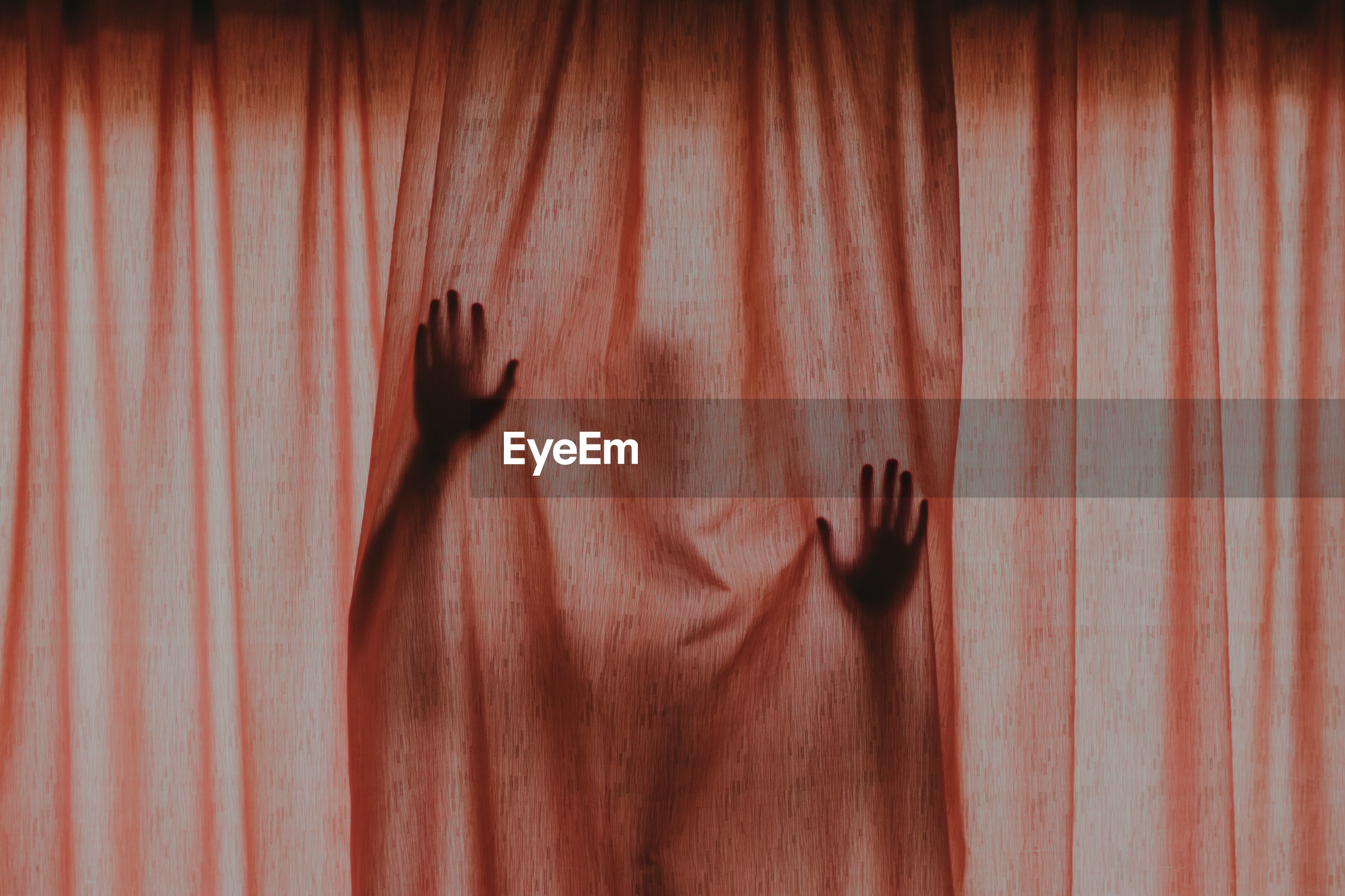 Person hiding behind brown curtain