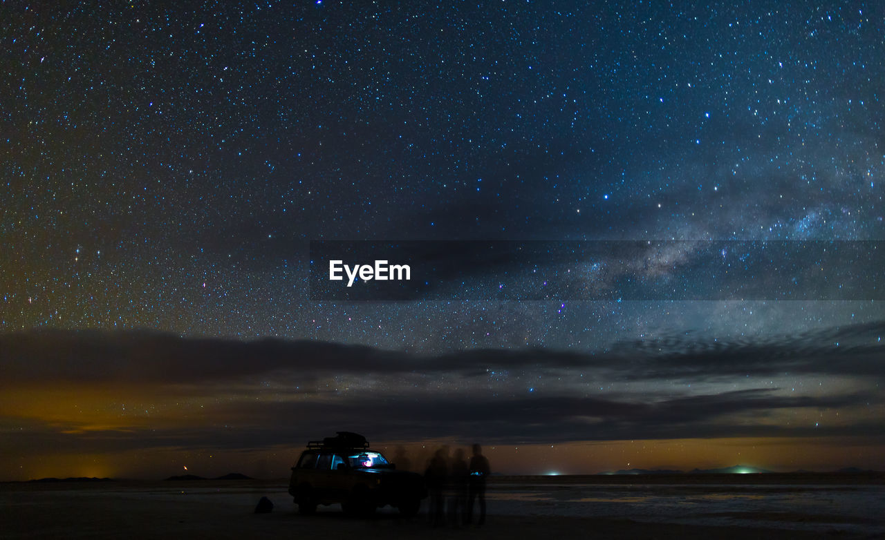 Blurred Motion Of People By Off-Road Vehicle At Salar De Uyuni Against Constellation
