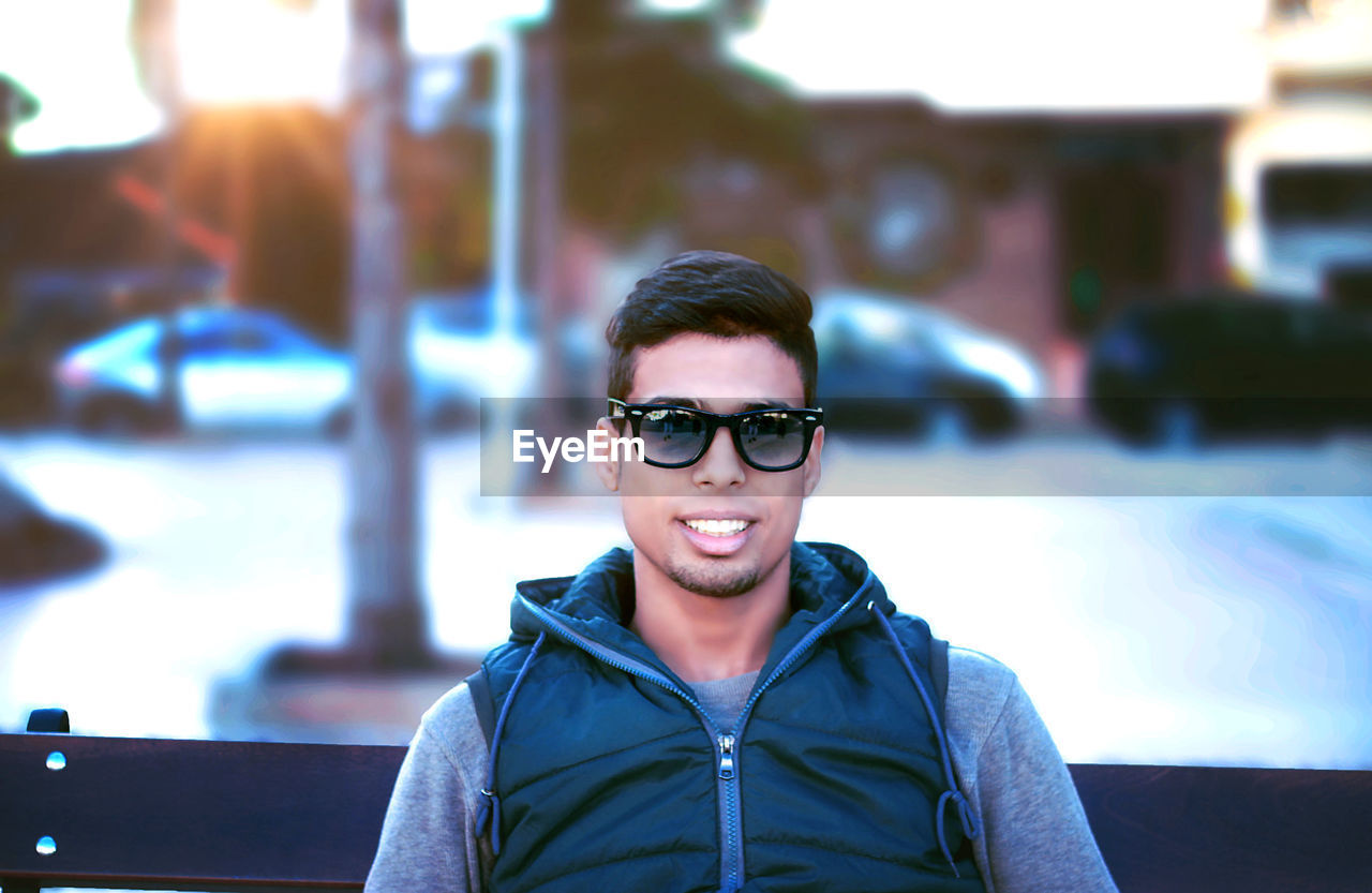 real people, one person, young men, portrait, young adult, glasses, lifestyles, focus on foreground, front view, leisure activity, smiling, fashion, casual clothing, looking at camera, sunglasses, headshot, happiness, architecture, men, outdoors