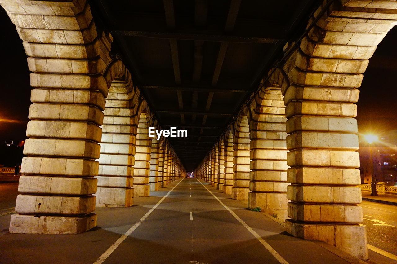 Empty road under bridge in illuminated city at night