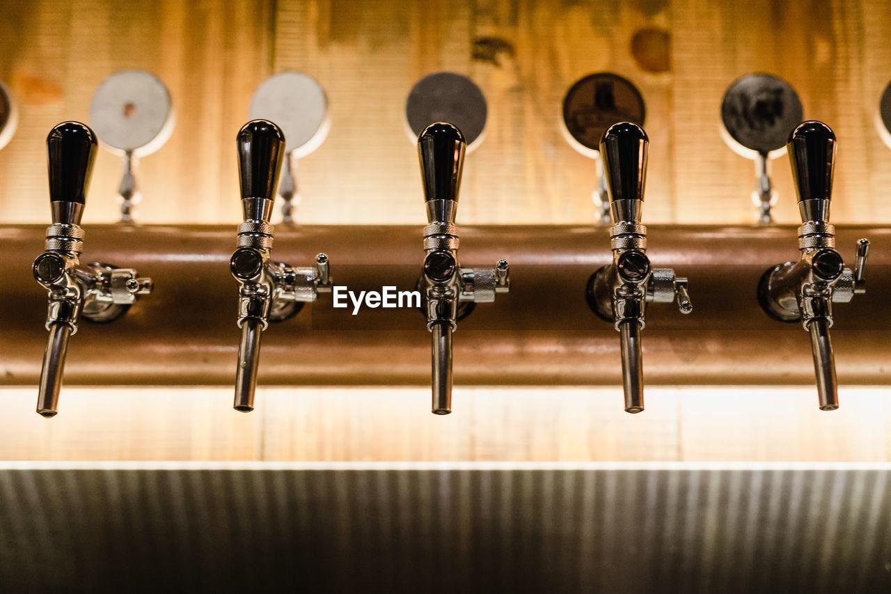 Close-up of beer taps at bar counter