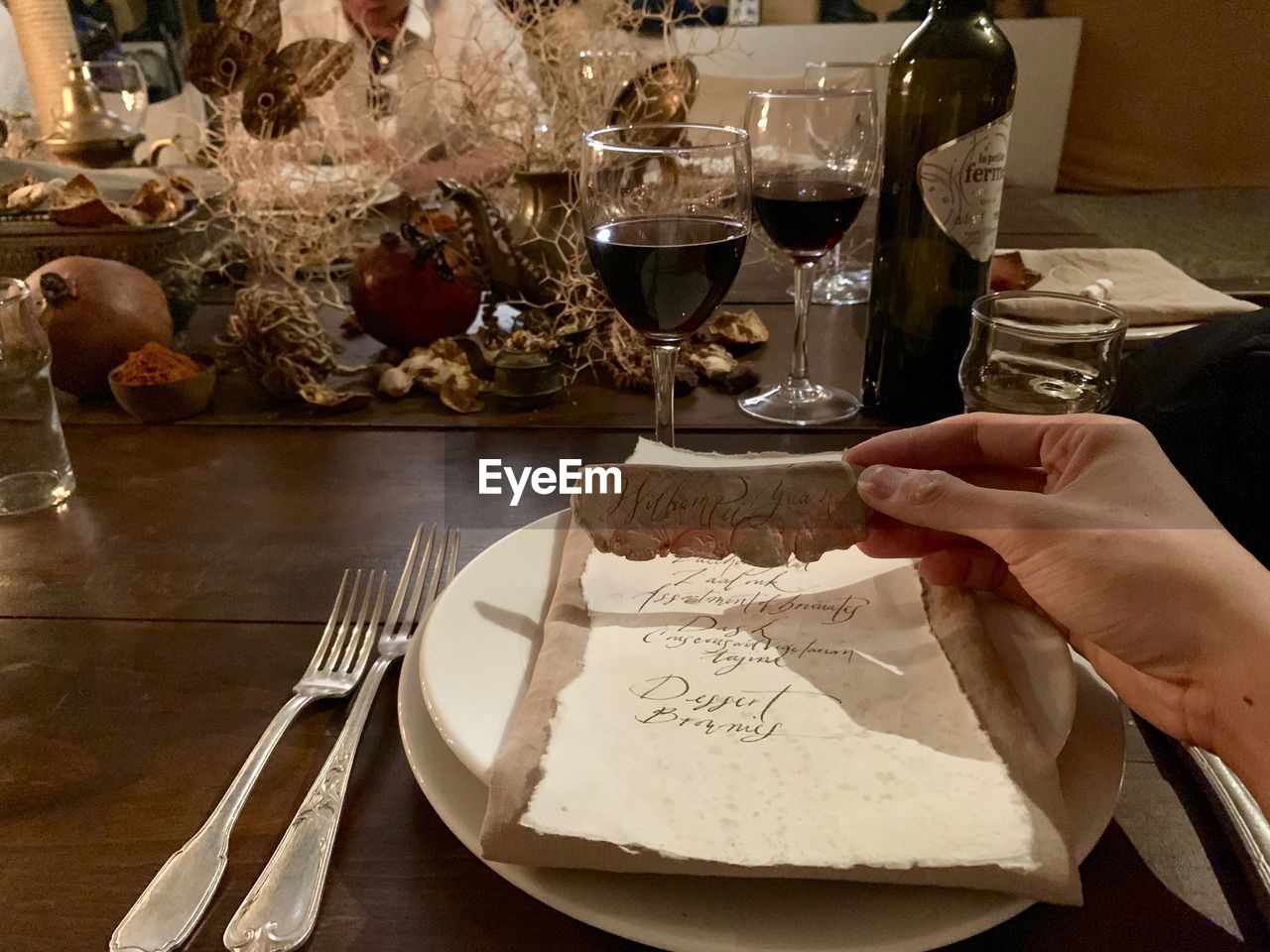 human hand, food and drink, hand, glass, human body part, drink, table, real people, one person, refreshment, food, indoors, holding, alcohol, wineglass, drinking glass, household equipment, freshness, unrecognizable person, wine, finger, red wine