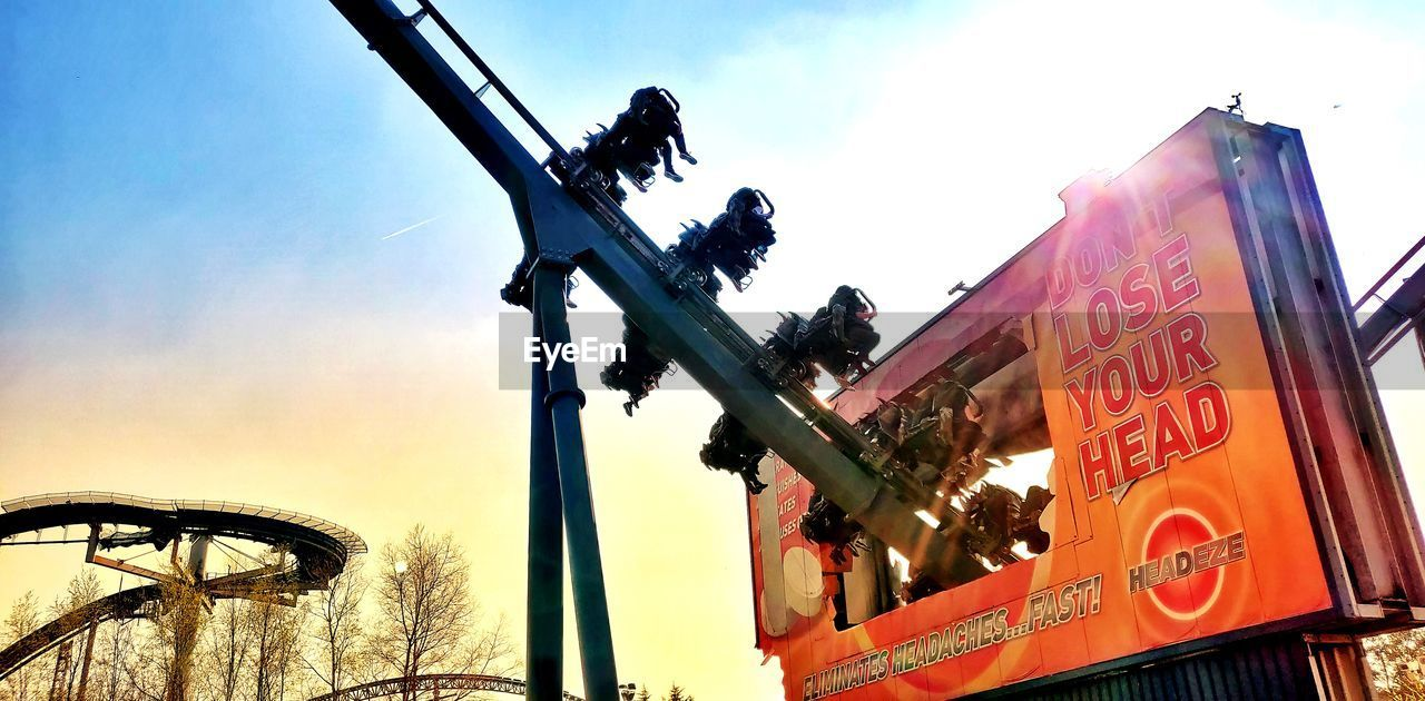 sky, low angle view, nature, text, communication, sign, architecture, outdoors, day, built structure, no people, cloud - sky, city, building exterior, sunset, orange color, machinery, western script, bicycle, amusement park