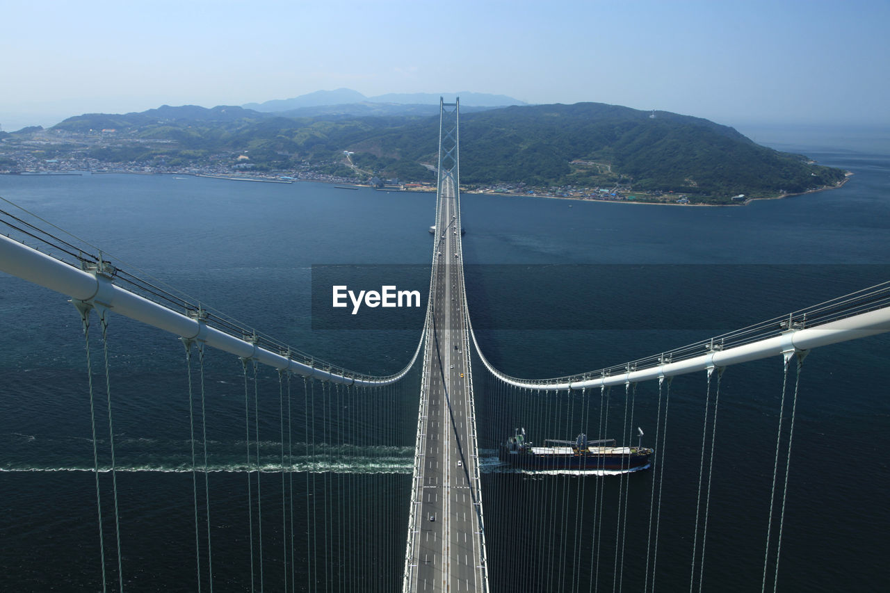 High Angle View Of Suspension Bridge Over Boat Sailing In Sea