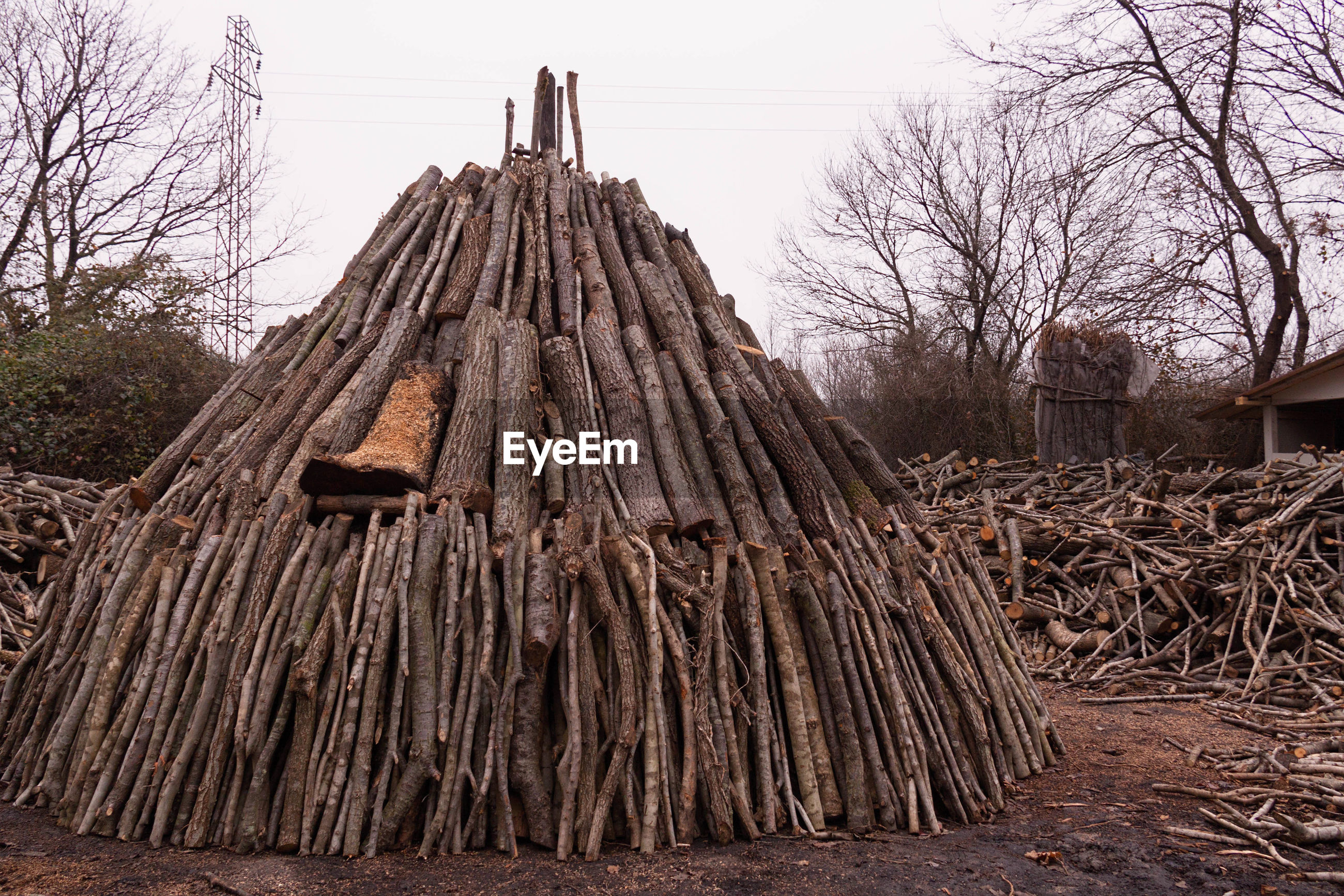 Stack of firewood on field against clear sky