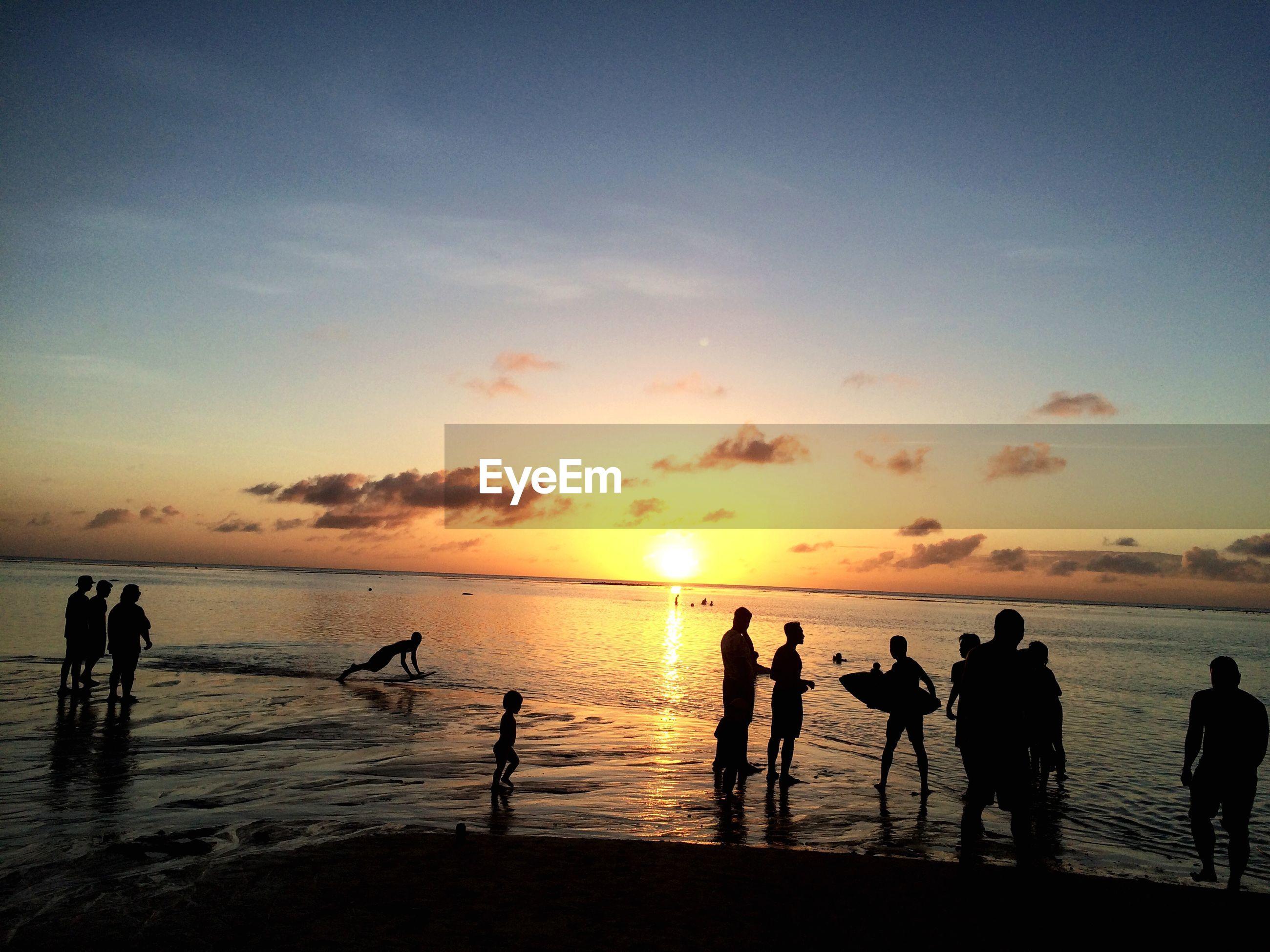 Tourists watching sunset on beach