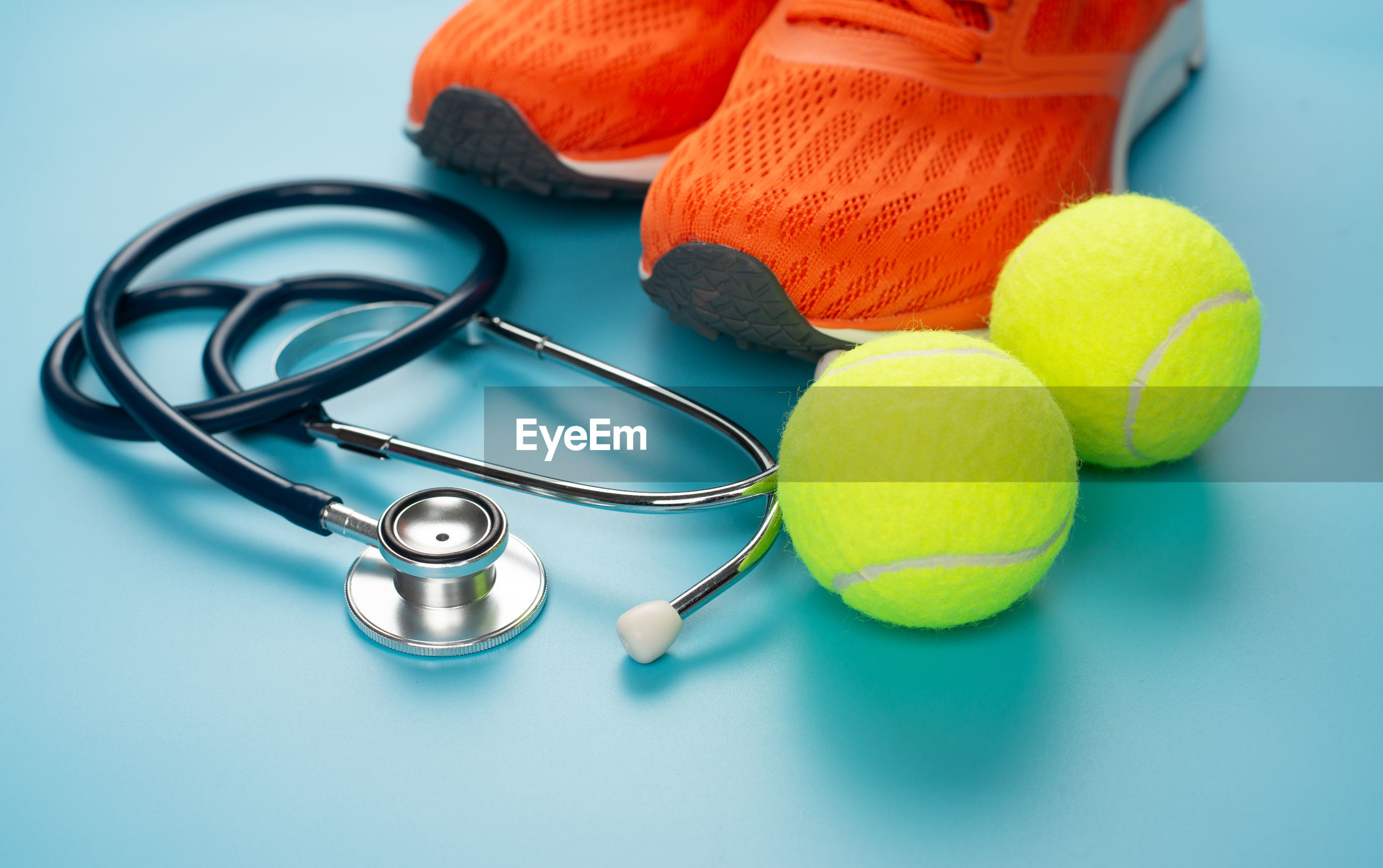 Close-up of shoes by stethoscope and tennis balls against blue background