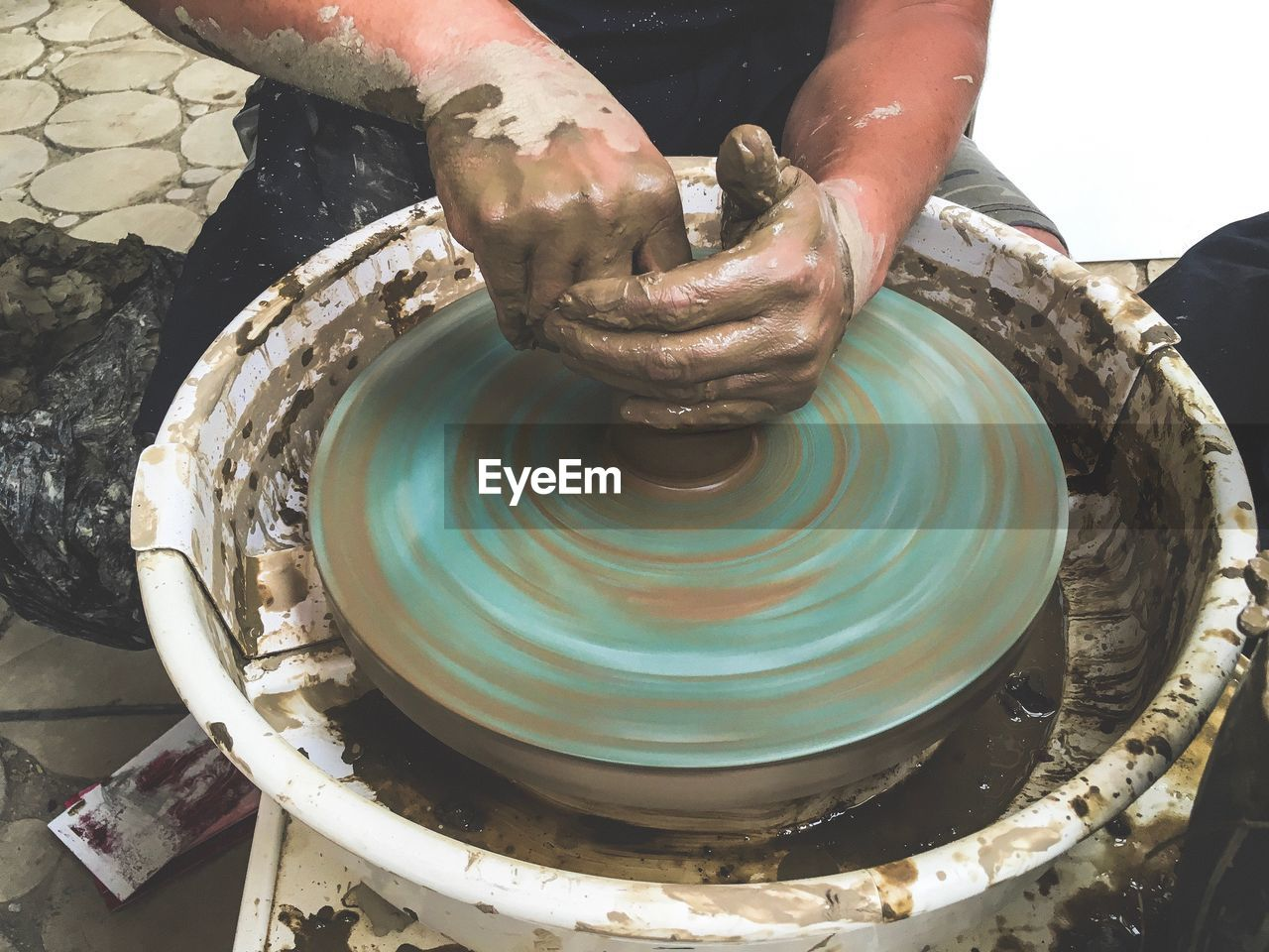 Midsection of craftsperson making pottery at workshop