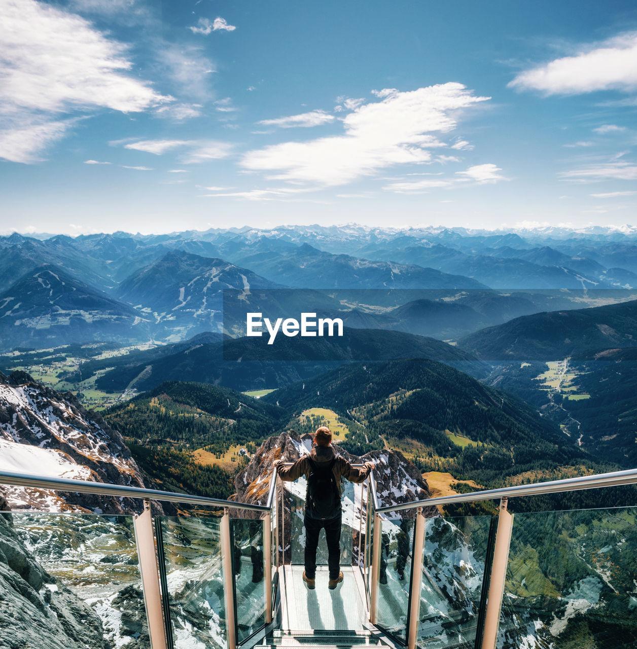 Man standing on footbridge over mountains against sky