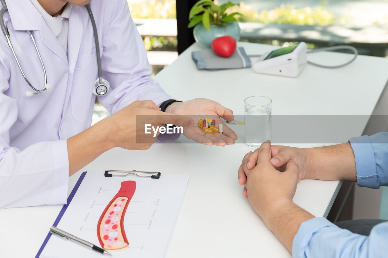 Midsection of doctor giving medicine to patient at clinic