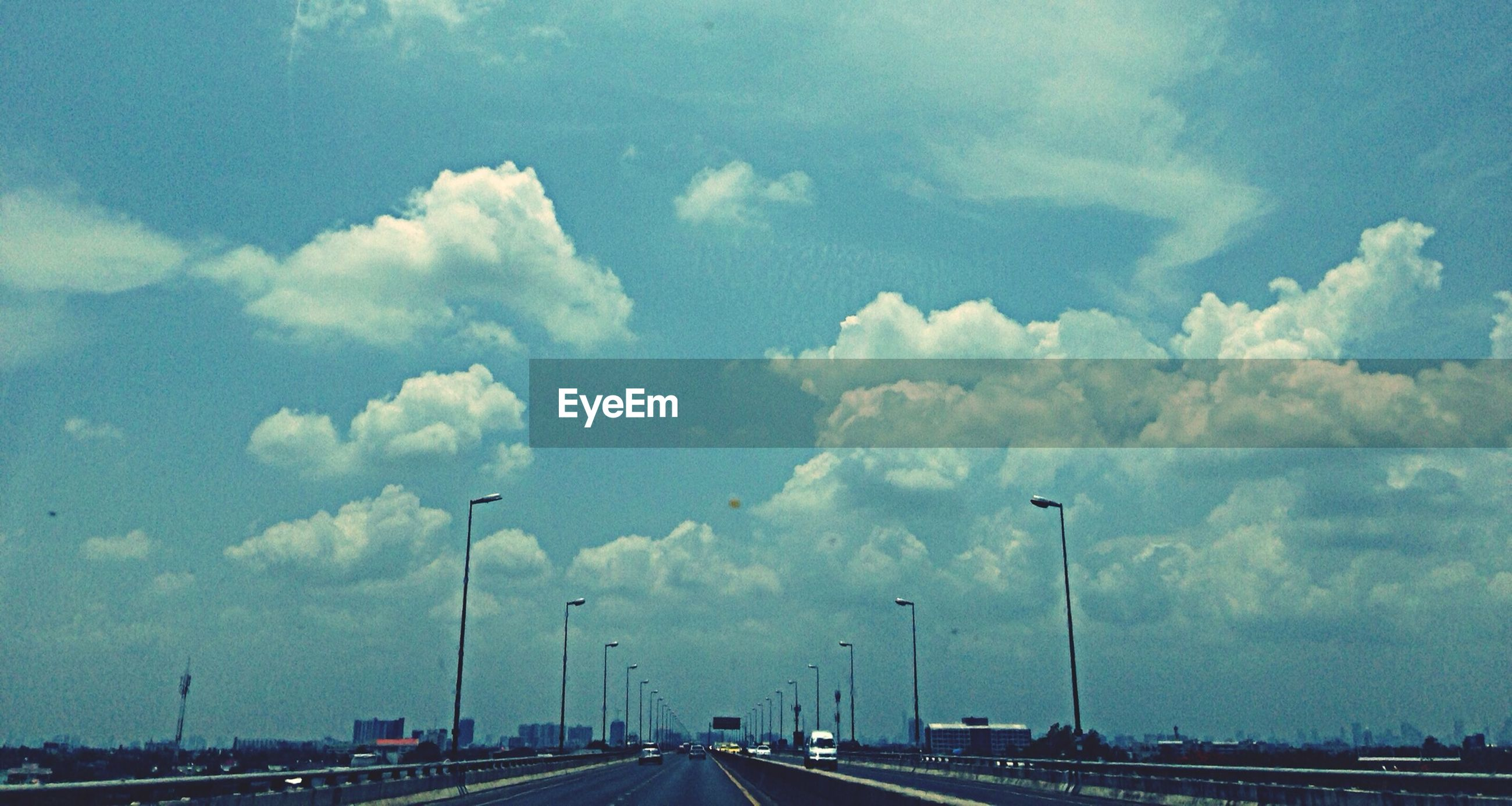 sky, the way forward, transportation, road, cloud - sky, street light, diminishing perspective, vanishing point, road marking, street, car, cloudy, cloud, blue, empty, land vehicle, outdoors, built structure, no people, highway