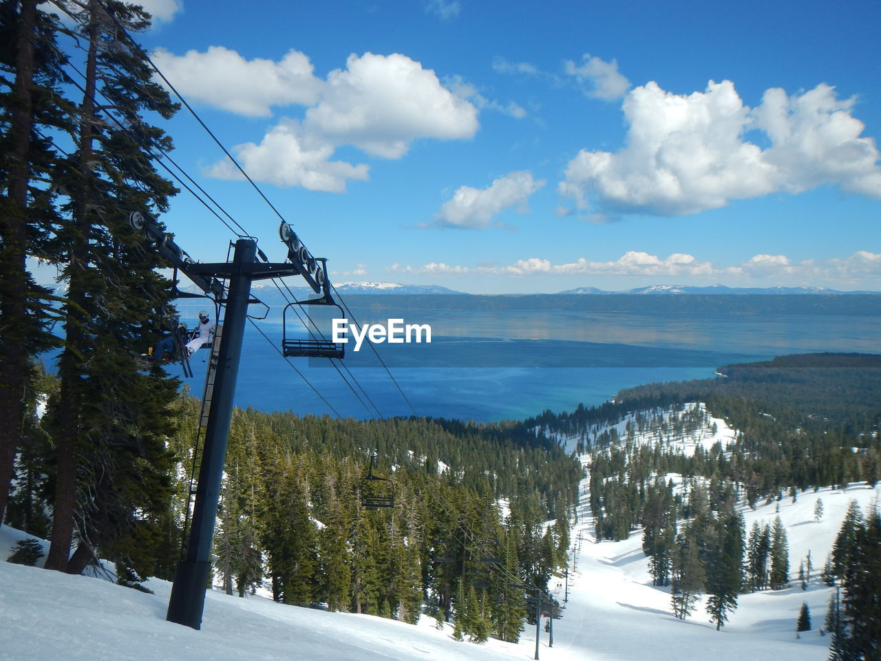 Scenic View Of Mountain Range And Lake Tahoe Against Cloudy Sky