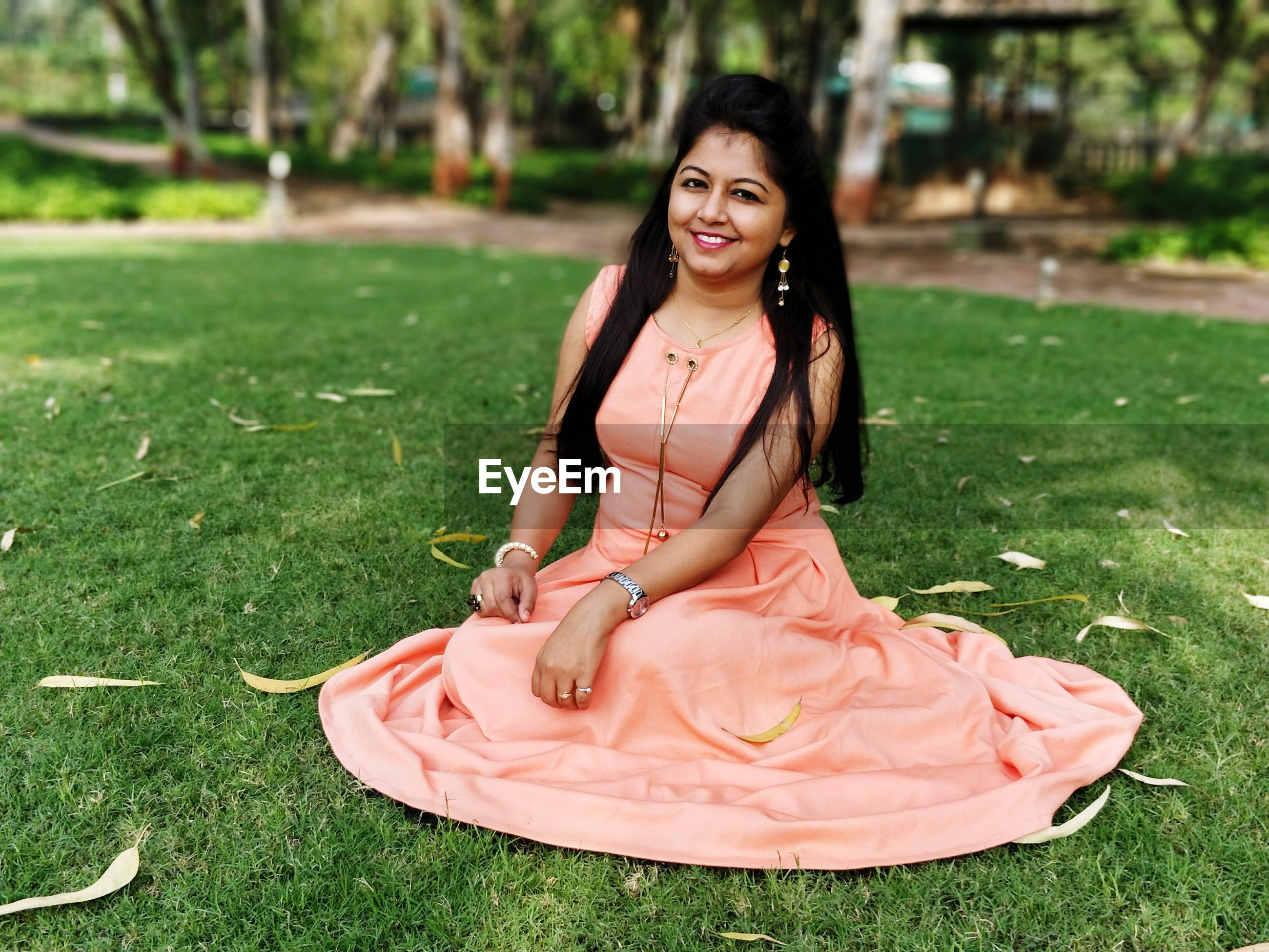 Portrait of smiling young woman sitting on field at park