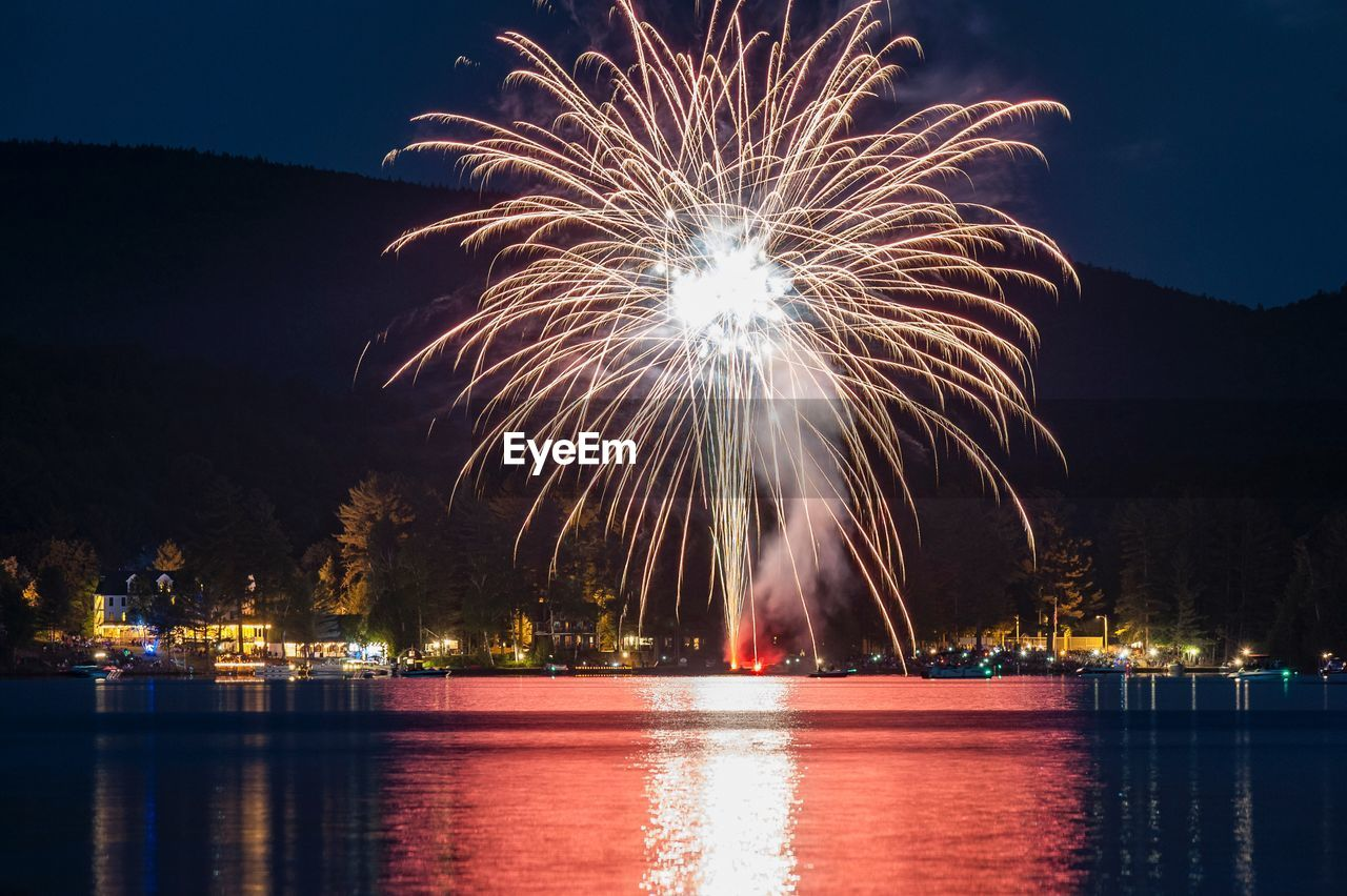 Illuminated fireworks by lake against sky at night